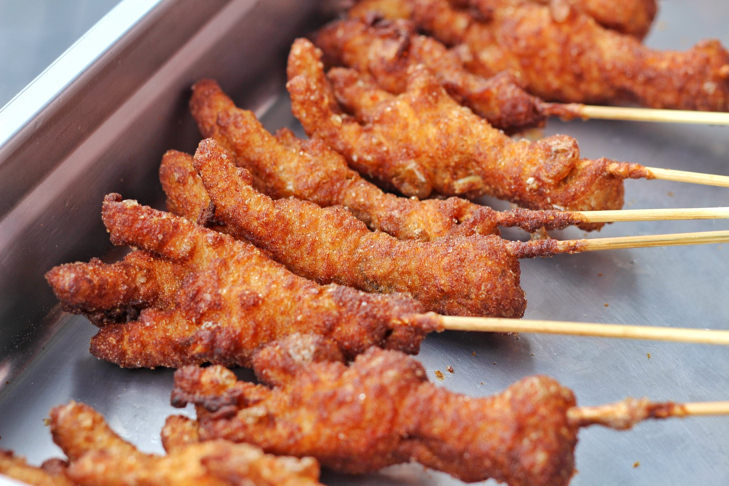 Crispy chicken feet served on a stick.