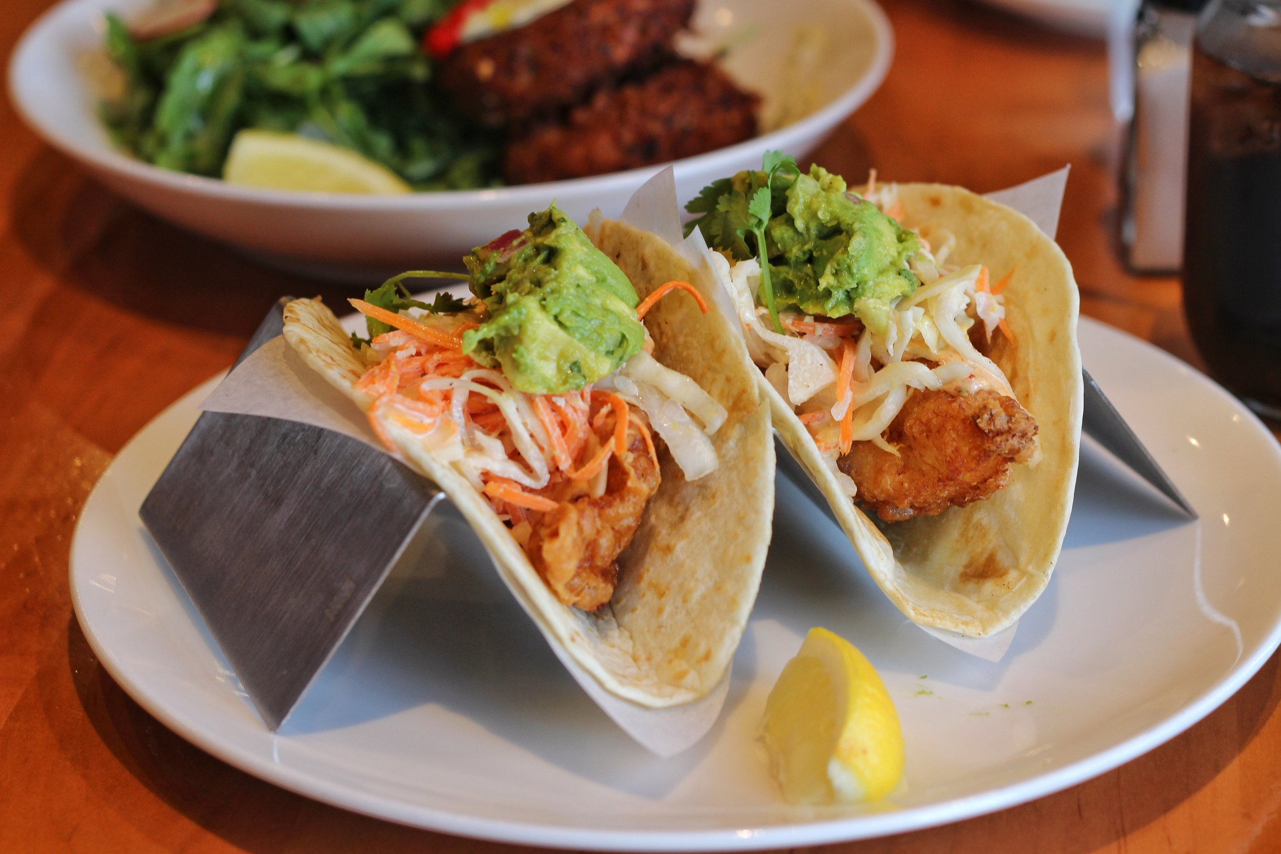 Baja Fish Tacos  – beer battered white fish, 2 homemade flour tortillas, citrus slaw, chipotle aioli, guacamole