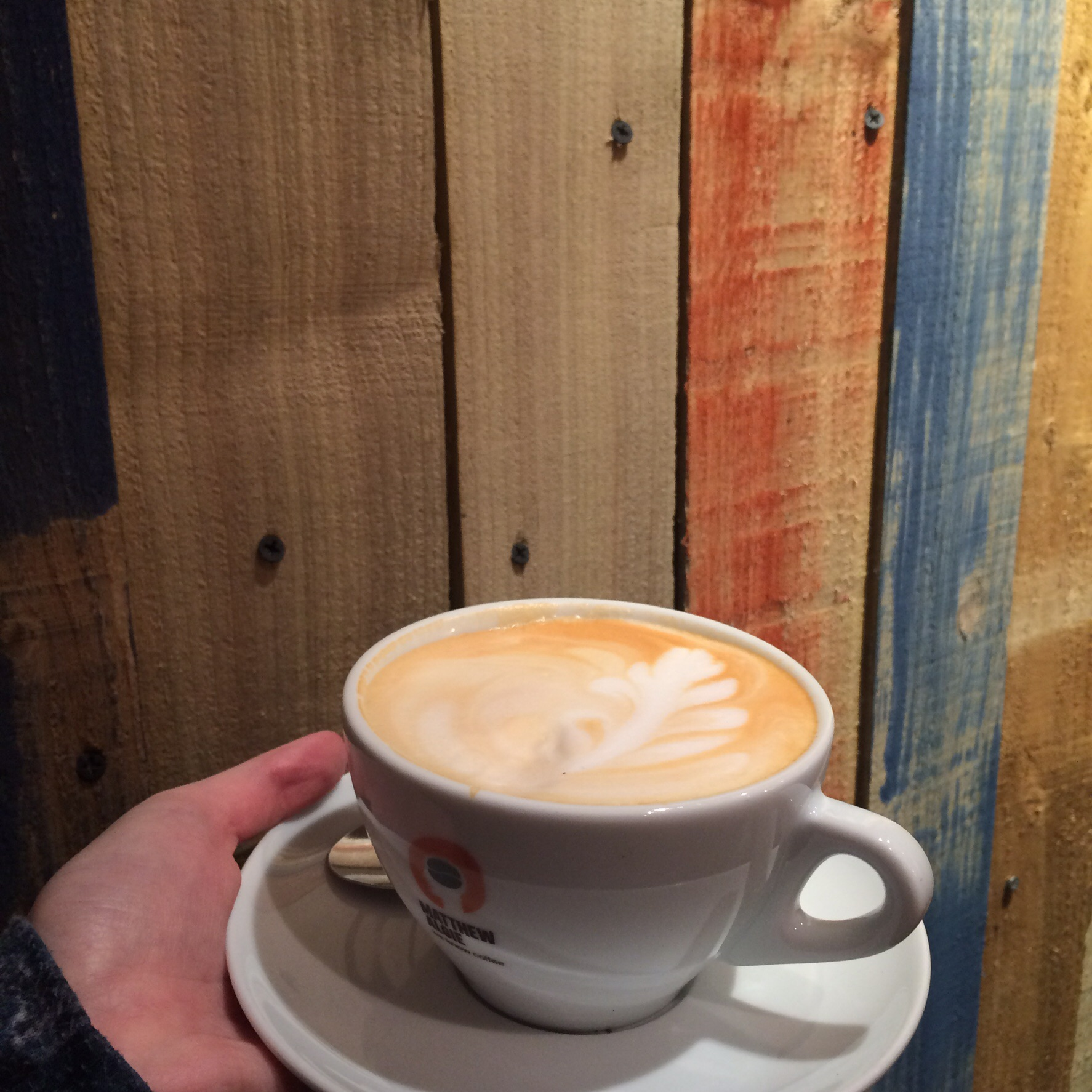 My vanilla rooibos latte against the earthy wall of The Caffeine Drip.