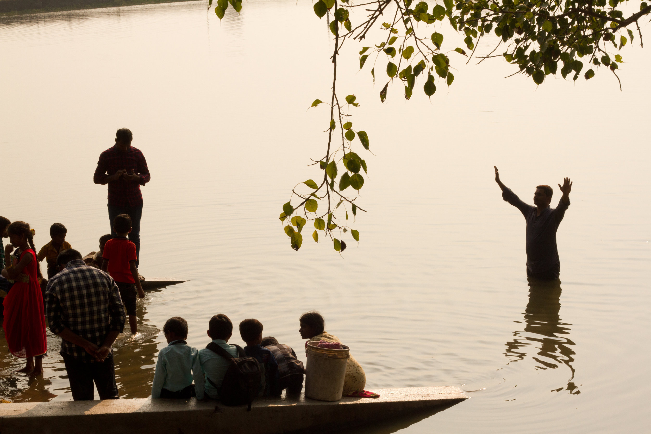Baptism in a small lake. Believers say Amen and Hallelujah and raise their hands a lot.