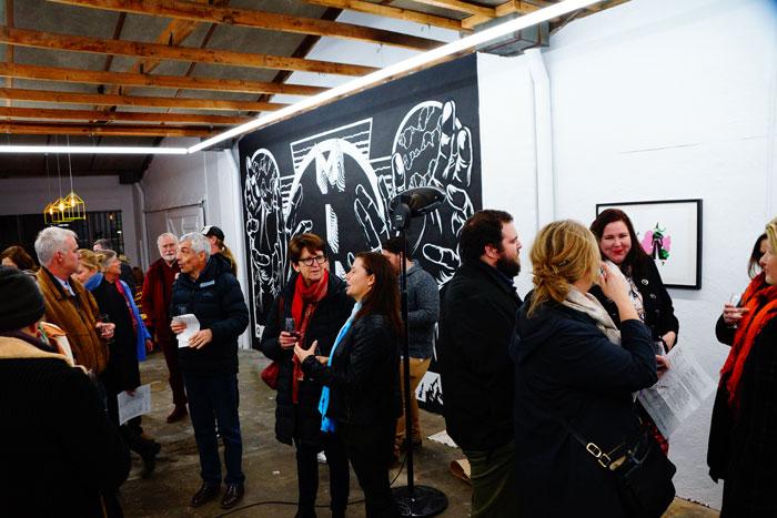 Georgia Hill and James Jirat Patradoon's mural as life swirls around it.