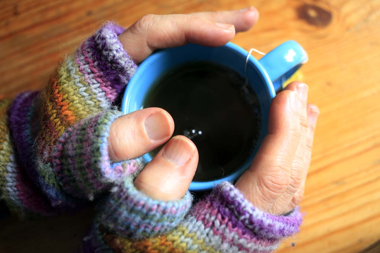 hands cold with gloves holding coffee cup