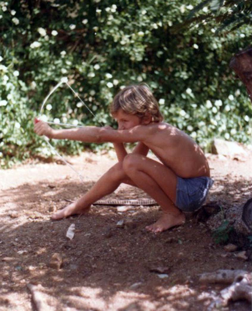 Young boy pulling bow and arrow on warm sand.