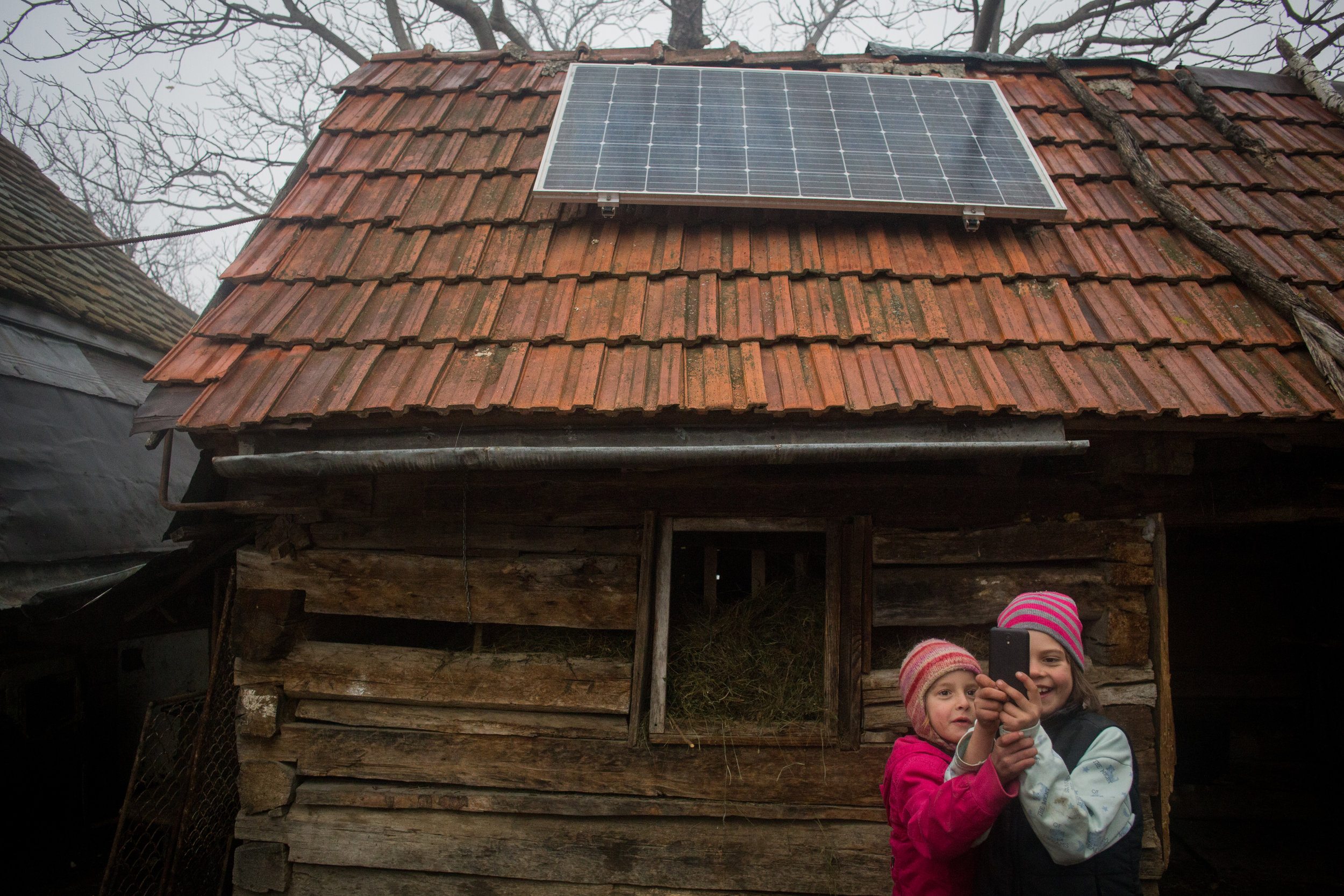 HOLBAV •  Mariana (7) and Claudia (9) Stoicheciu take pictures with their phones; thanks to solar panels, they can recharge batteries at home.