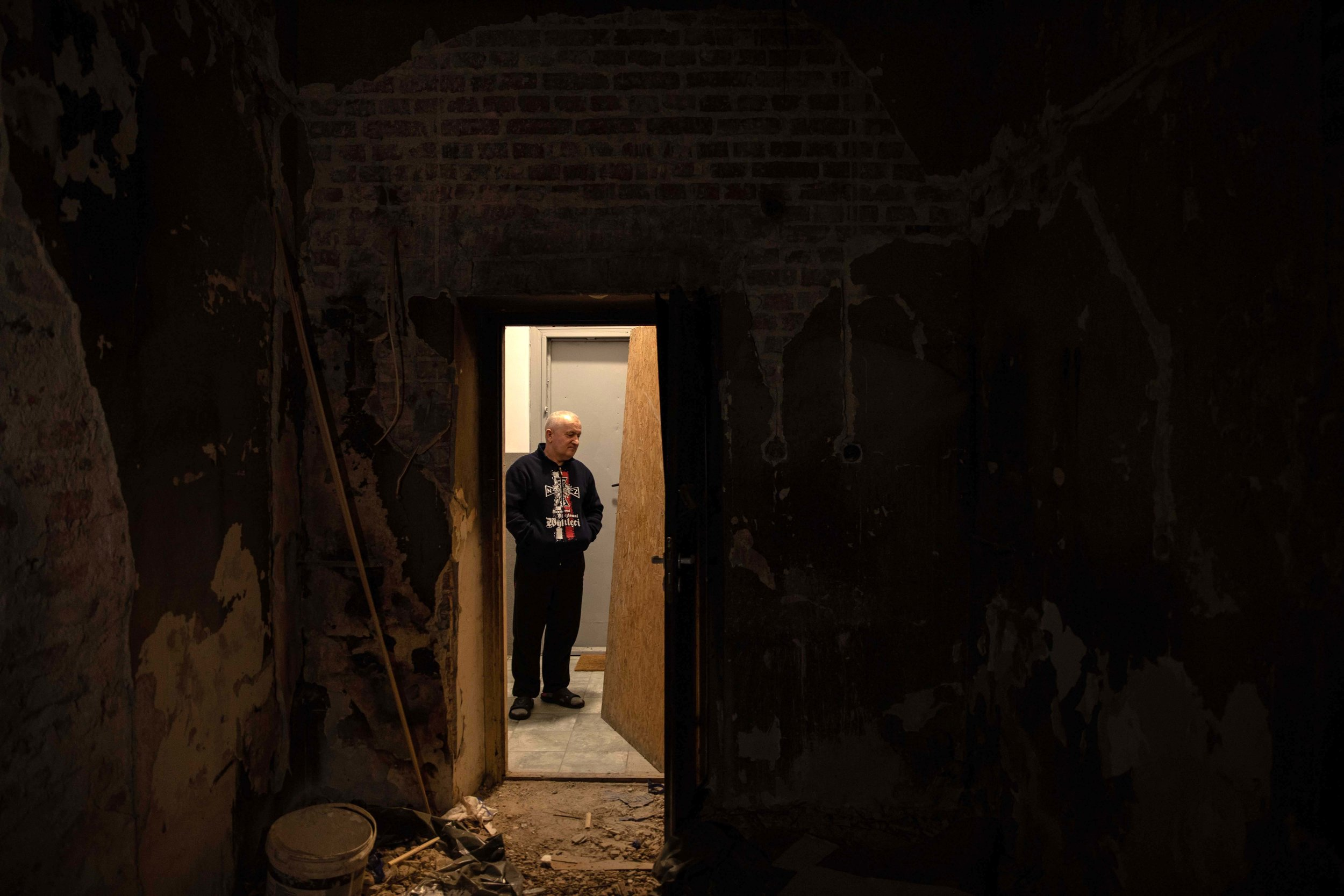 WARSAW • Stanislaw, a friend, stands in the hall of the flat Ryszard Kowalski moved into in the 1970s with his wife and her parents. Forty years on, nothing has been done to improve the building.