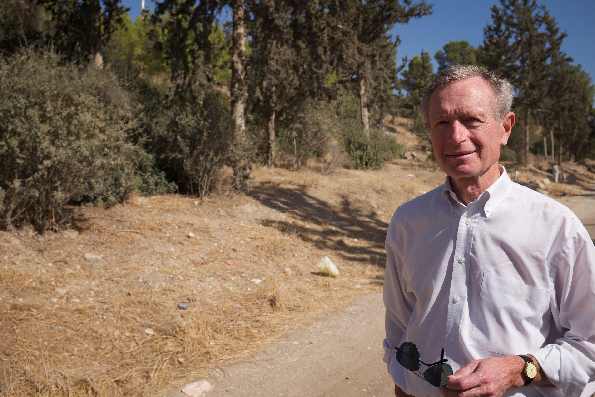 Erik Ader in Bayt Nattif met naaldbomen voor zijn vader geplant door JNF op de achtergrond