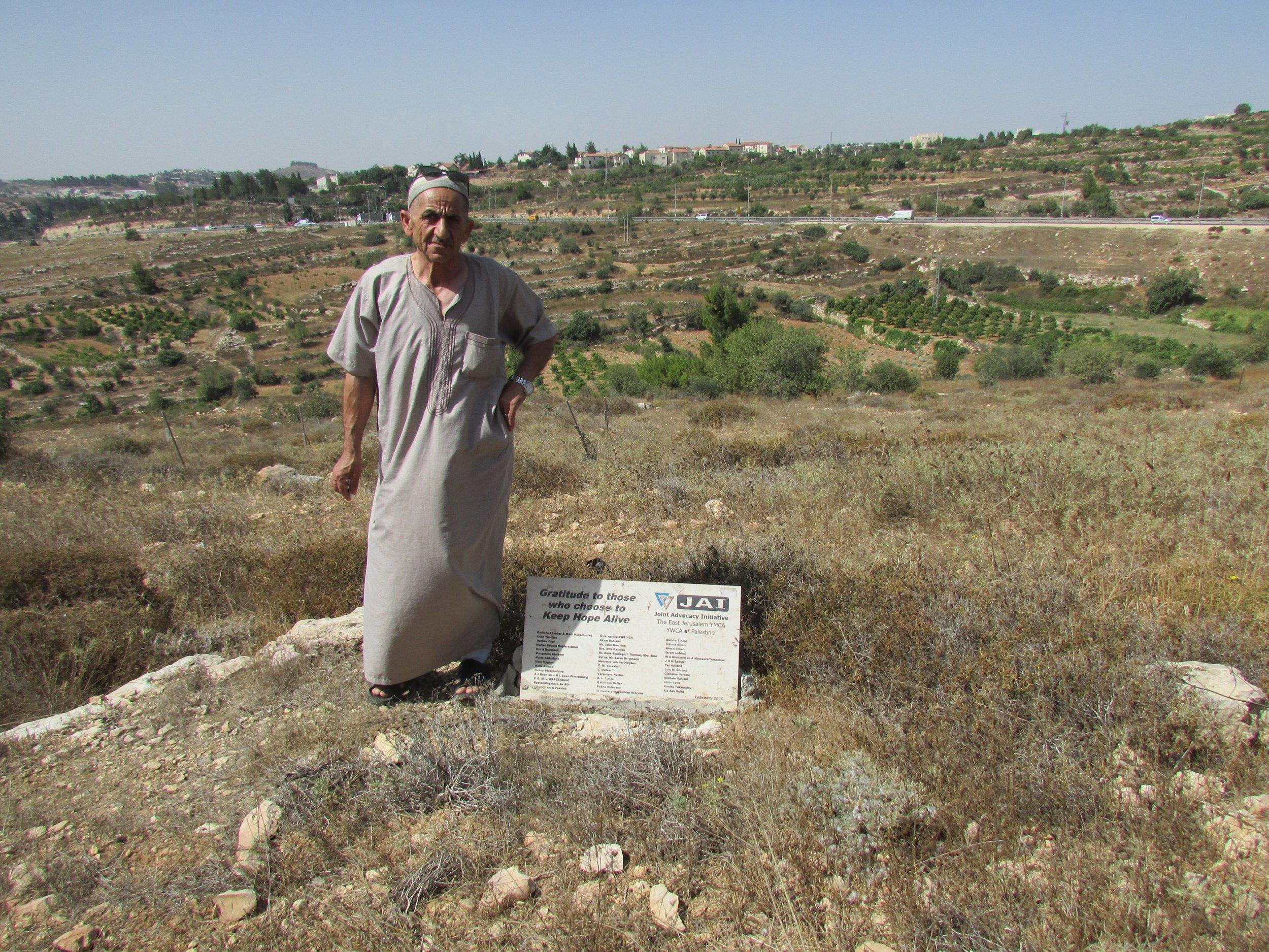 Hasan Mohmad Sbeih naast de plaquette met de namen van sponsoren