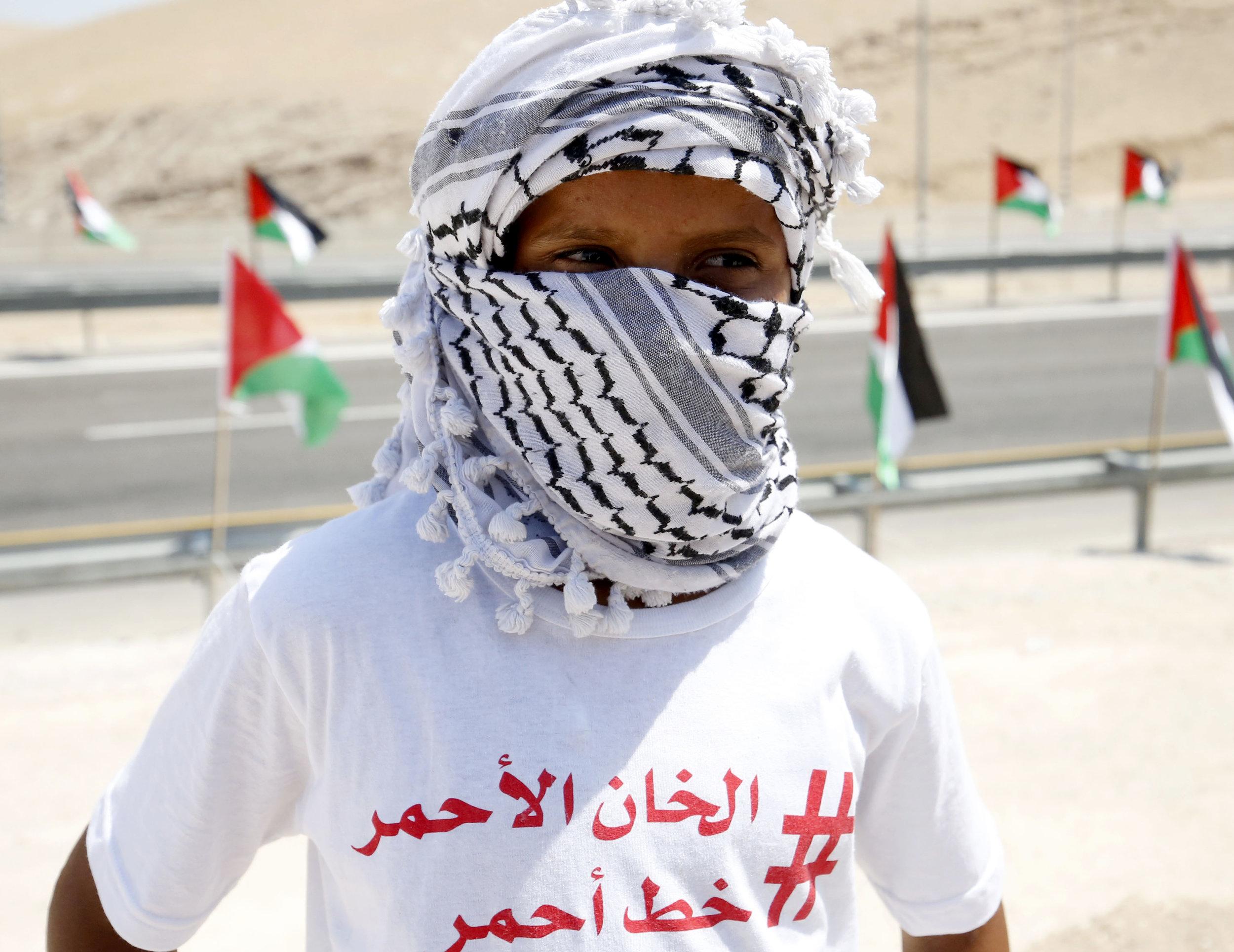 """Op het t-shirt van deze Palestijnse demonstrant staat """"Khan al-Ahmar is een rode line"""" inspelend op het woord ahmar wat rood betekent in het Arabisch [Getty]"""