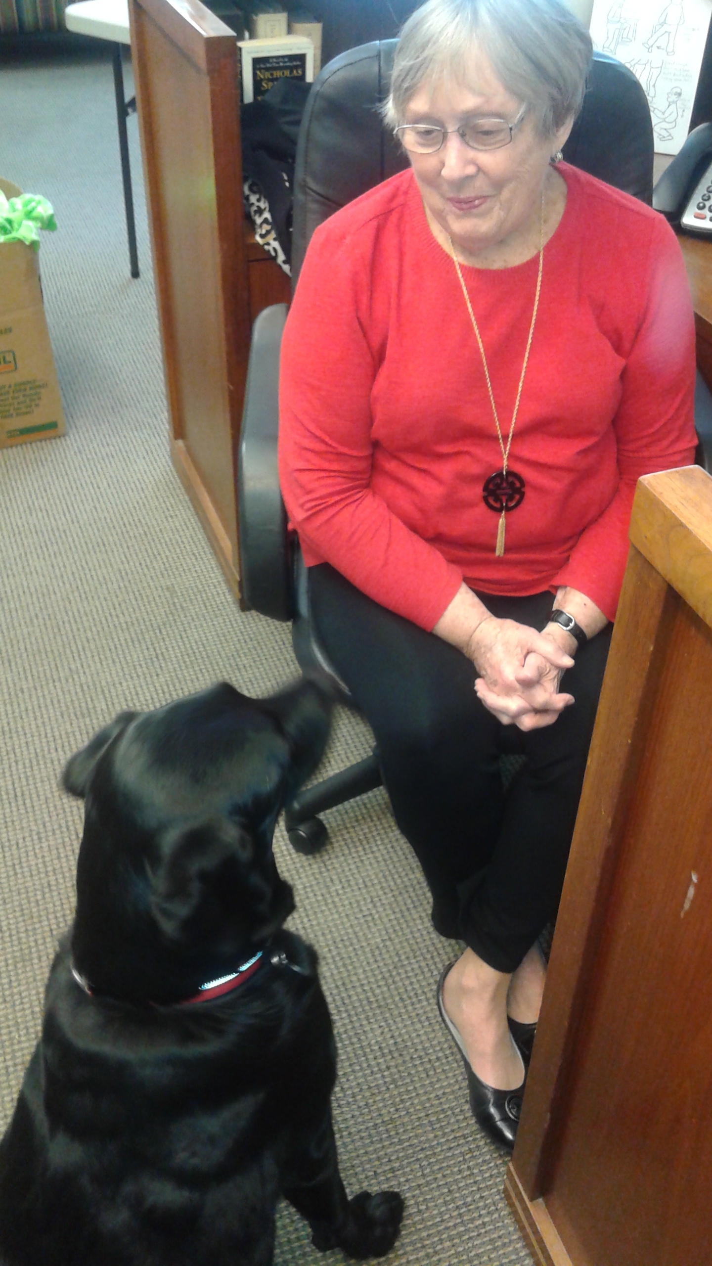 Peggy Roberts and Spike share a conversation at the reception desk.