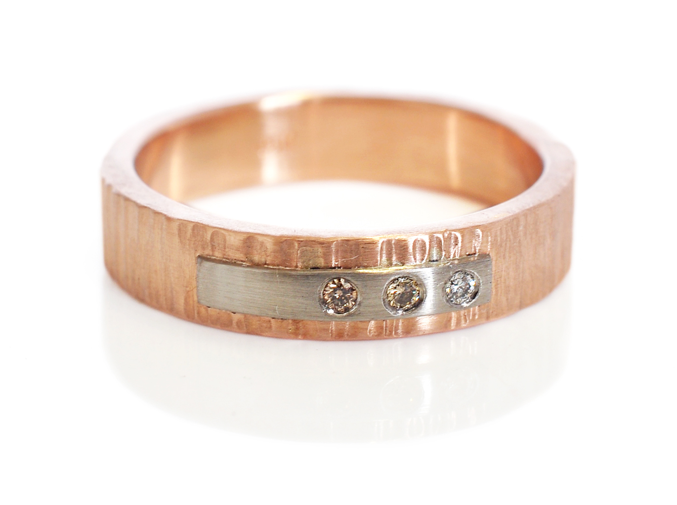 For Terese a 4mm wide 14k red gold band with a linear hammered finish, a 500 palladium strip and 3 flush-set diamonds in shades of champagne and white.