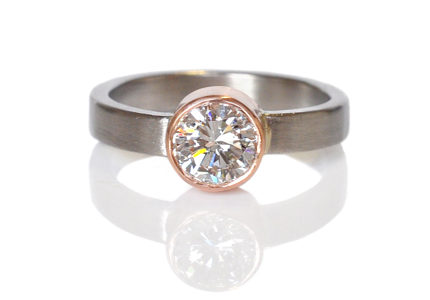 Kristy and Matt brought in this blindingly bright brilliant cut Moissanite stone and designed a sleek and simple setting with a little extra width on the band for a pinch of toughness. 14k red gold bezel set into a wide 950 palladium band.