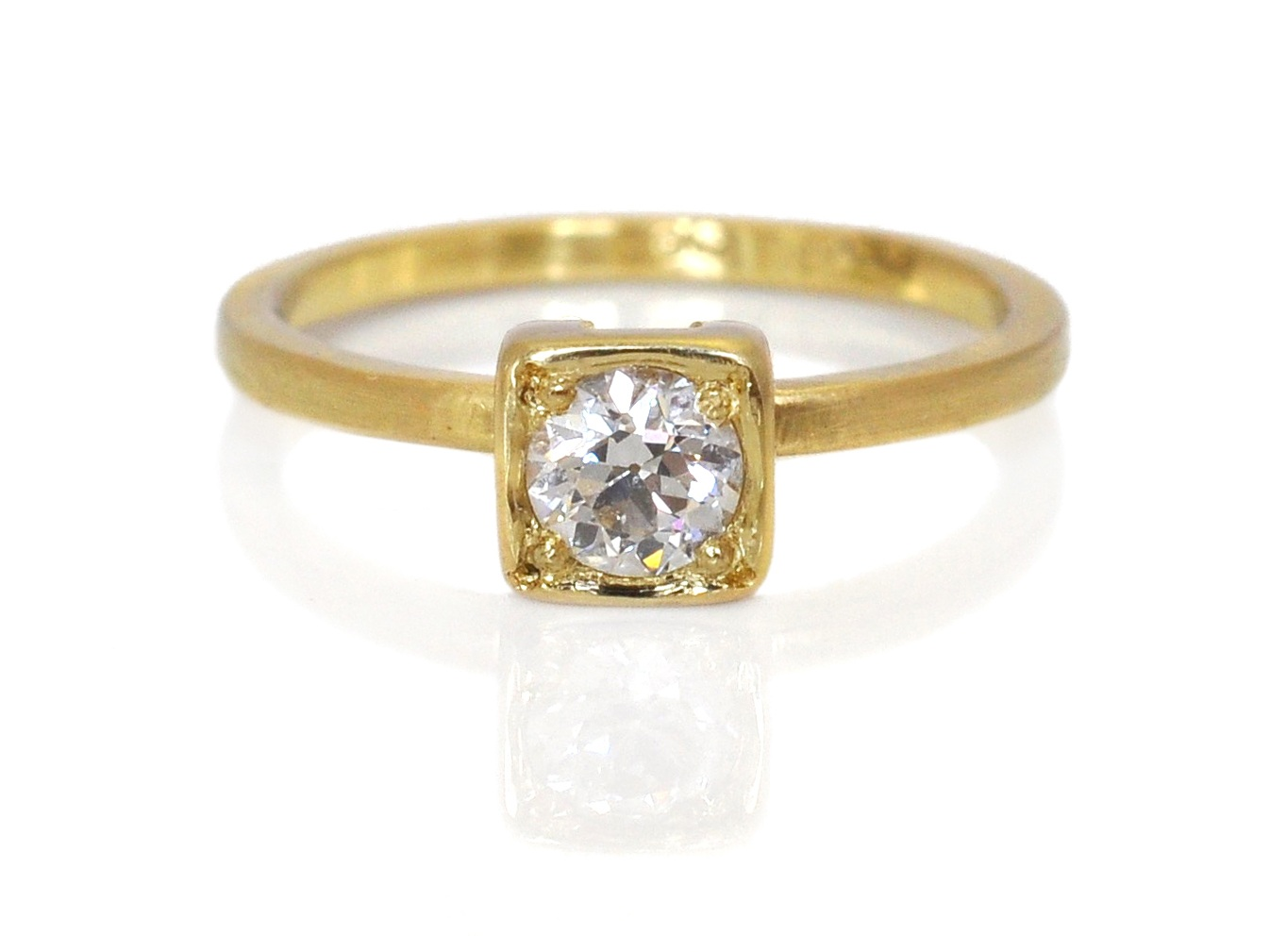 This unique custom remount is a mix of old and new in many ways. The diamond was a family heirloom and the new hand-fabricated 18k yellow gold setting was meant to mirror the original plate setting while adding a modern twist with the straight, clean lines.