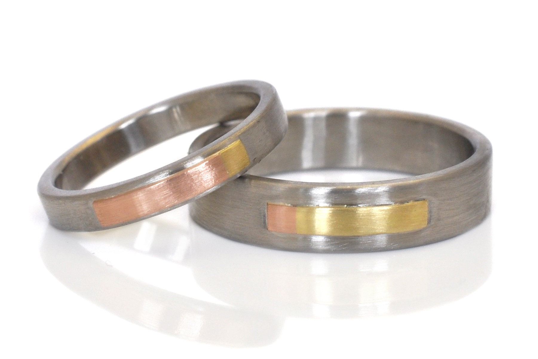 Custom complimentary wedding bands in mixed metals of 500 palladium, 14k red gold and 18k yellow gold with a sleek satin finish.  I love the subtle color change at the end of the Rivet strips.