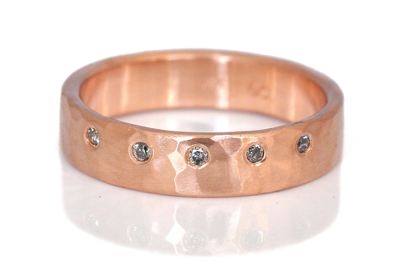 Shana wanted a hammered red gold band with flush-set diamonds, but we didn't want her engagement ring to cover them up. Solution: Diamonds on the edge, perfect for stacking! 4mm wide band in hammered 14k red gold with flush-set salt and pepper diamonds.