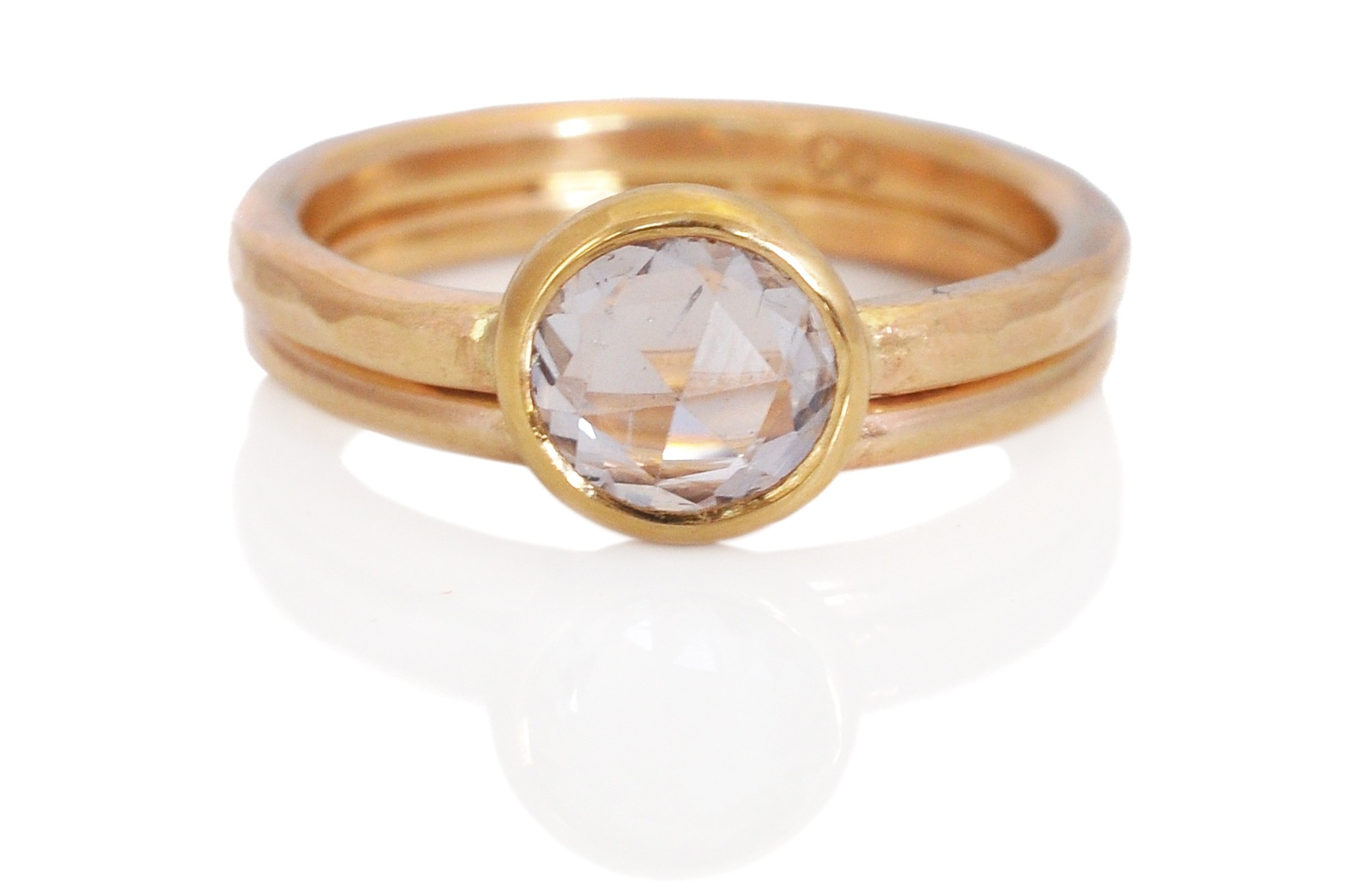 A pale pink rose cut sapphire in 14k yellow gold with a facet hammered finish