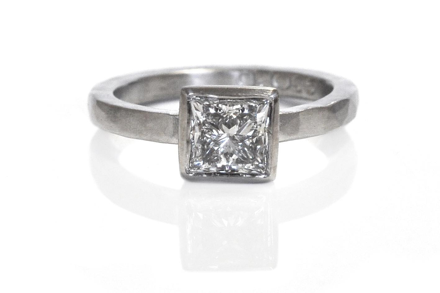 A sparkling princess cut diamond bezel set in hammered 950 palladium.