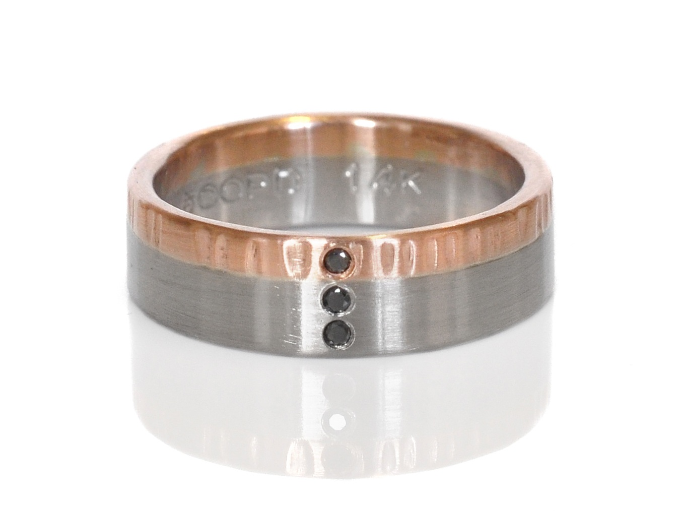 Modern mixed metal wedding band of linear hammered 14k red gold, satin finish 500 palladium and flush set black diamonds.