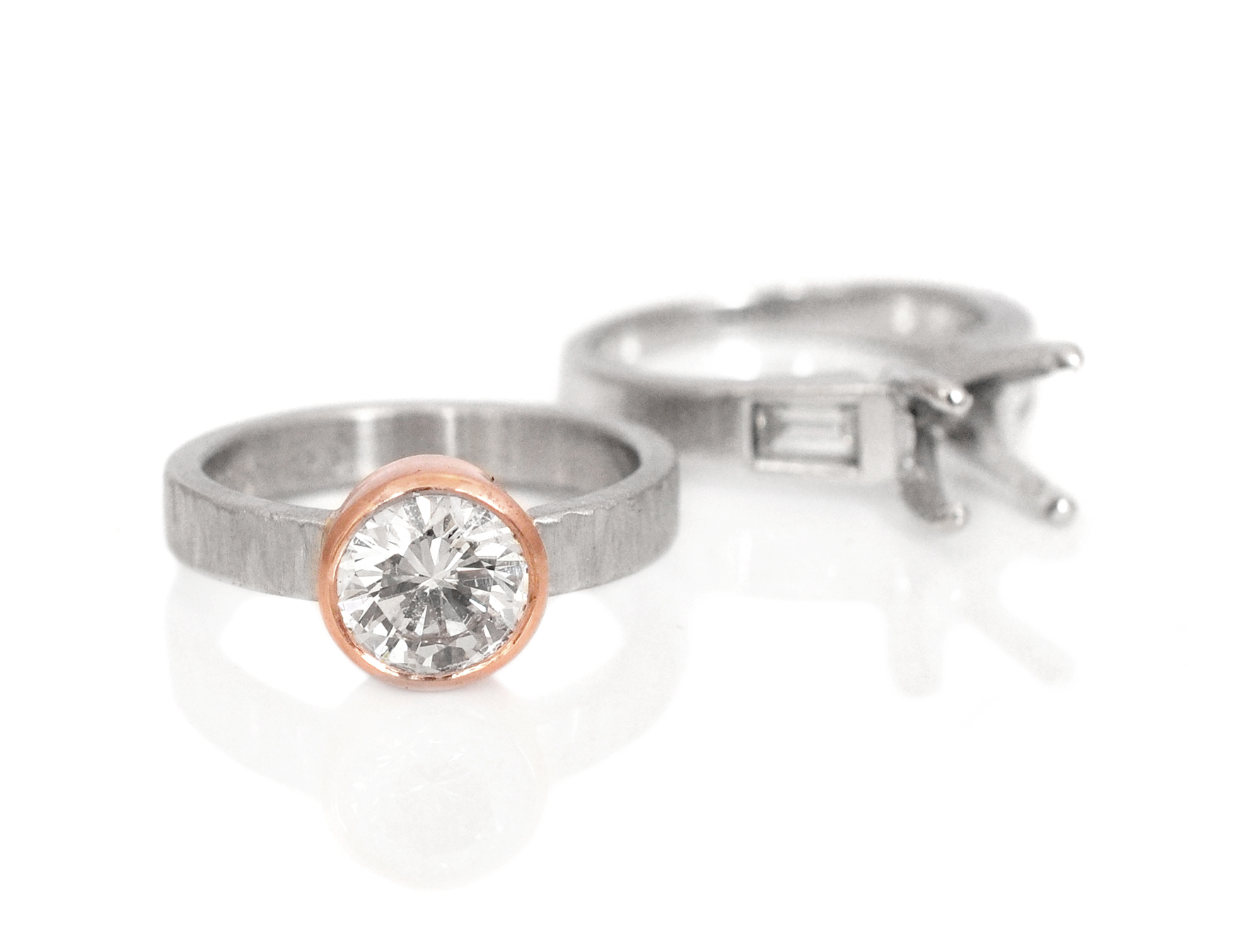 Nina wanted to update her beautiful diamond setting and fell in love with this mixed metal style. We re-set her diamond in a recycled 14k red gold bezel and inset it into the linear textured palladium band to keep the stone as low set as possible.