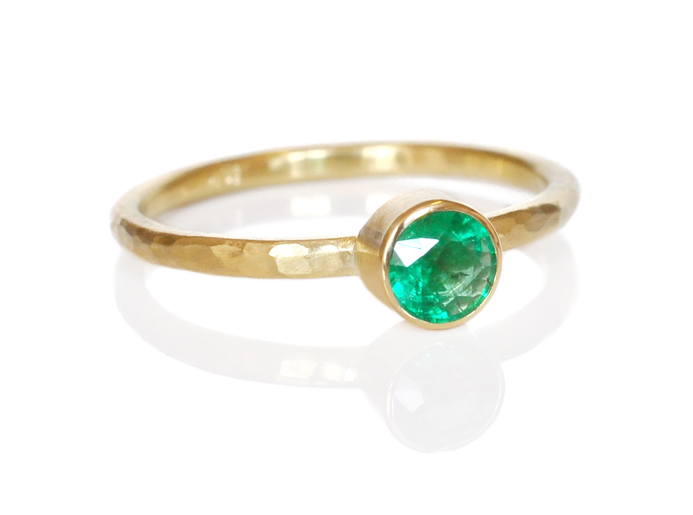 A brilliant cut emerald bezel set in 14k yellow gold on a hand-hammered round band.