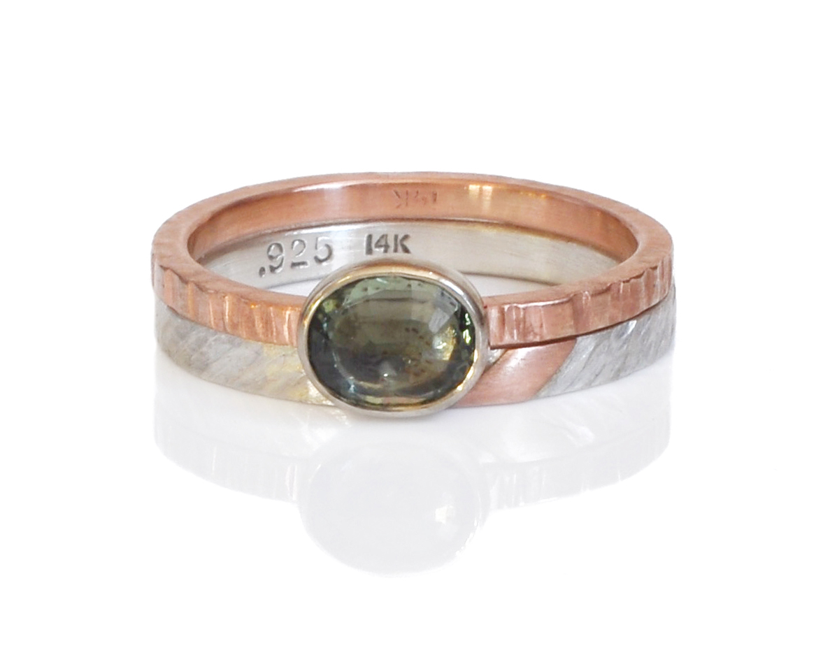 Amy paired this oval green sapphire in mixed metals of 14k red gold and 14k white gold bezel with a modern mixed metal band in diagonal hammered sterling silver with a 14k red gold accent.