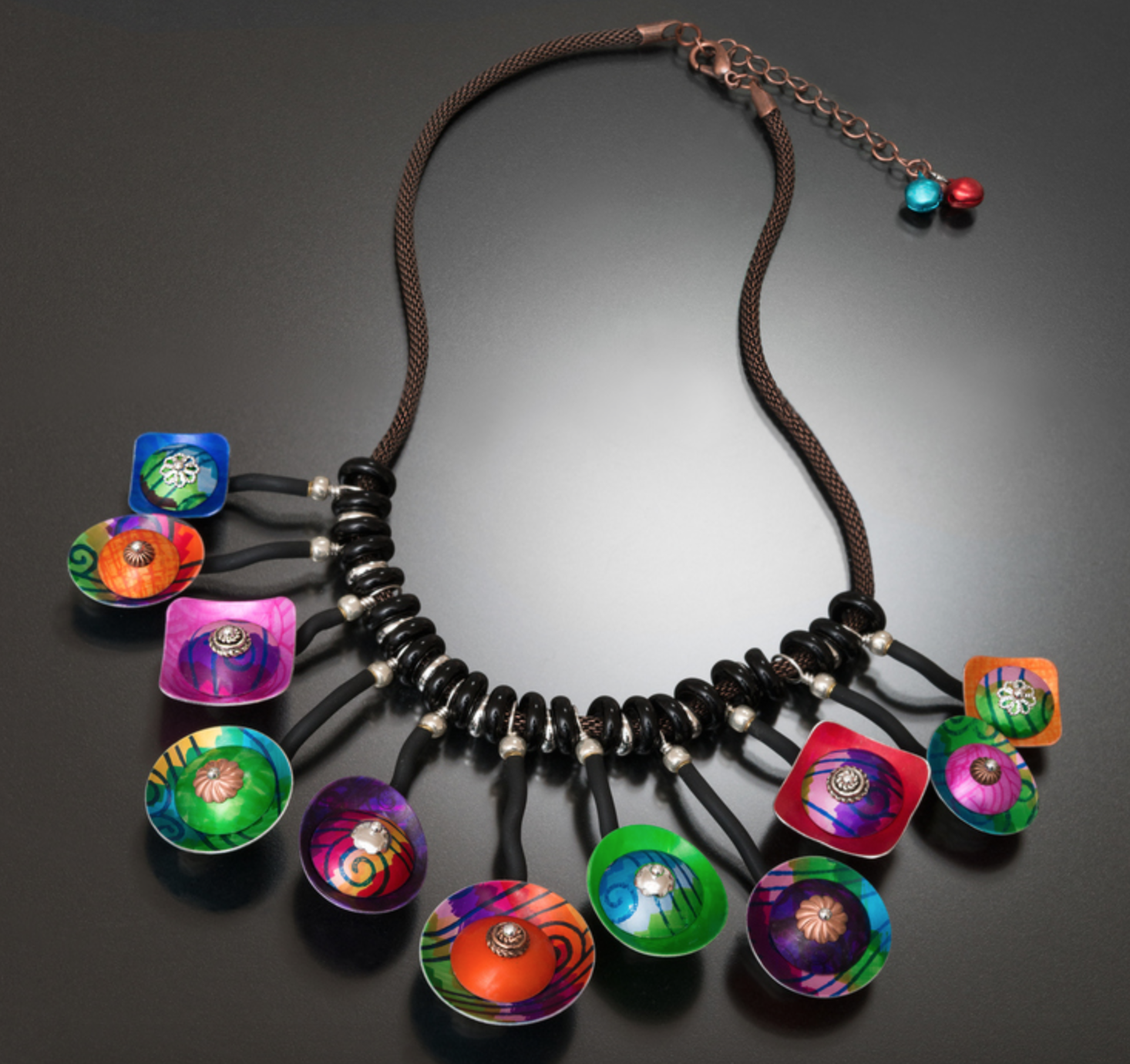 Dana McDaniel - http://danadesignstudio.comJewelry of mixed metals including copper, pewter, silver and hand-painted and heat-treated aluminum. Some with kiln-fired glass, set gemstones, river stones and vitreous enamels