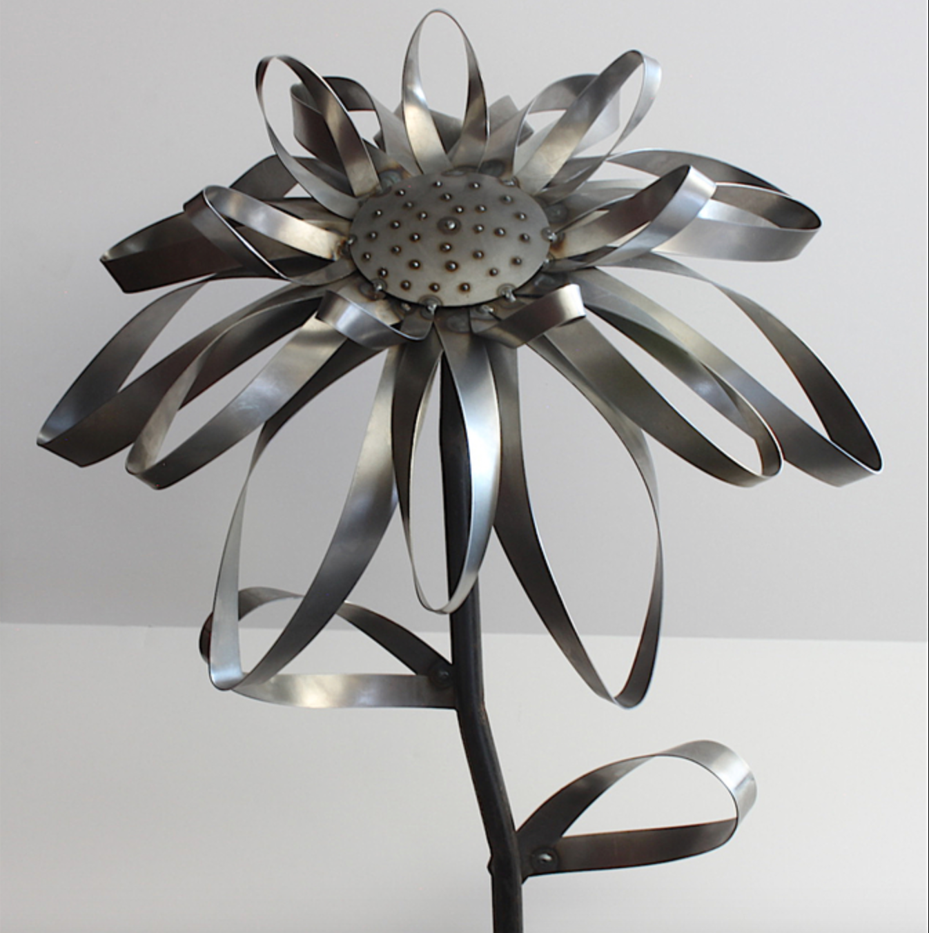 Rick Peerce - I hand make each flower out of 18 gauge steel.Each piece is cut, rolled and bent by hand.I then weld the pieces together to create the different flowers.