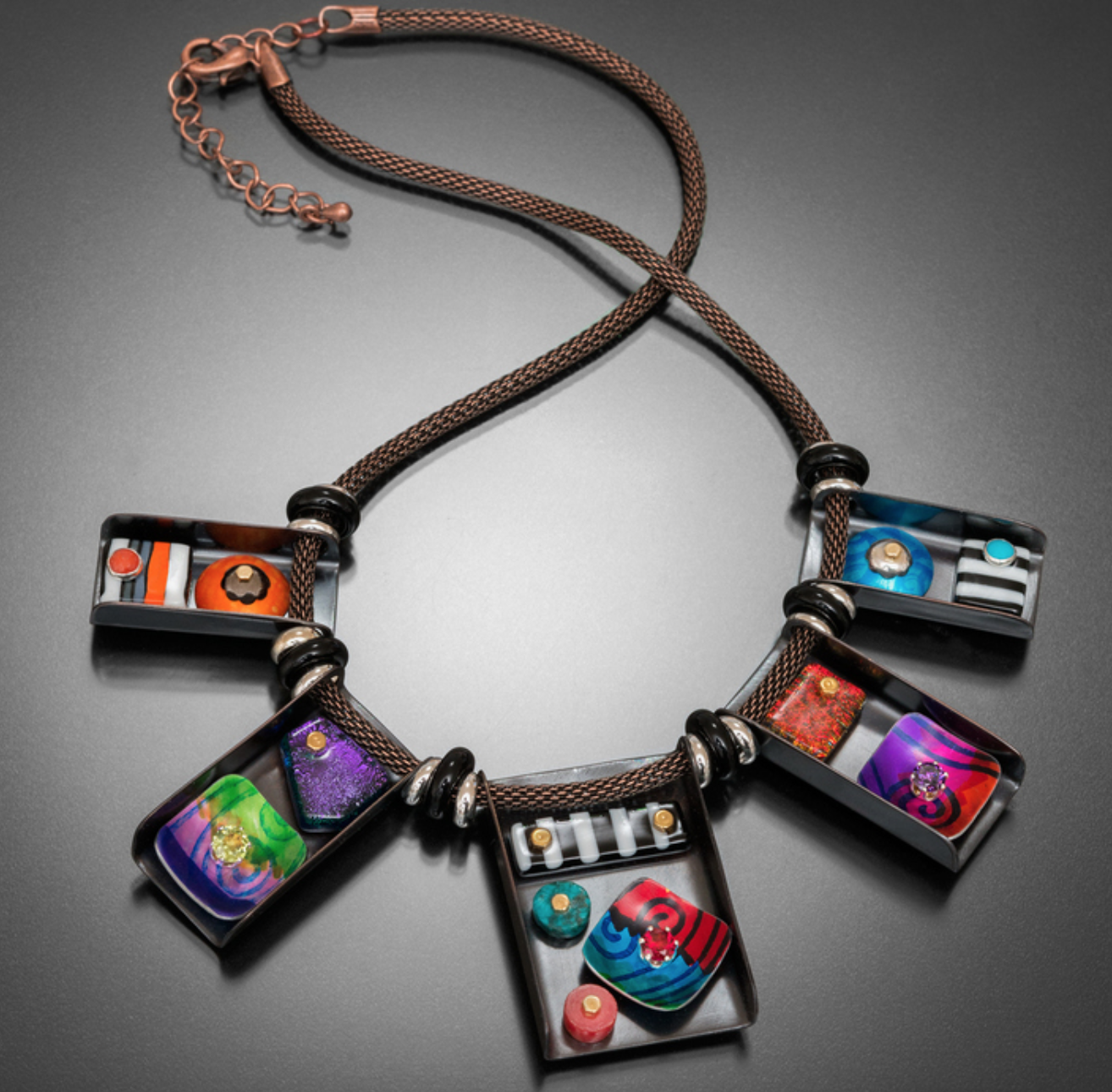 Dana McDaniel - http://danadesignstudio.comJewelry of mixed metals including copper, pewter, silver and hand-painted and heat-treated aluminum. Some with kiln-fired glass, set gemstones, river stones or vitreous enamels