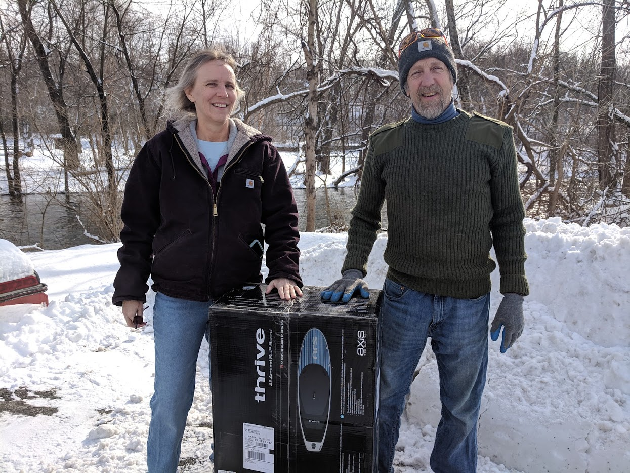 DRM's final contest winner, Sue, and her husband standing with their prize, a new paddleboat.