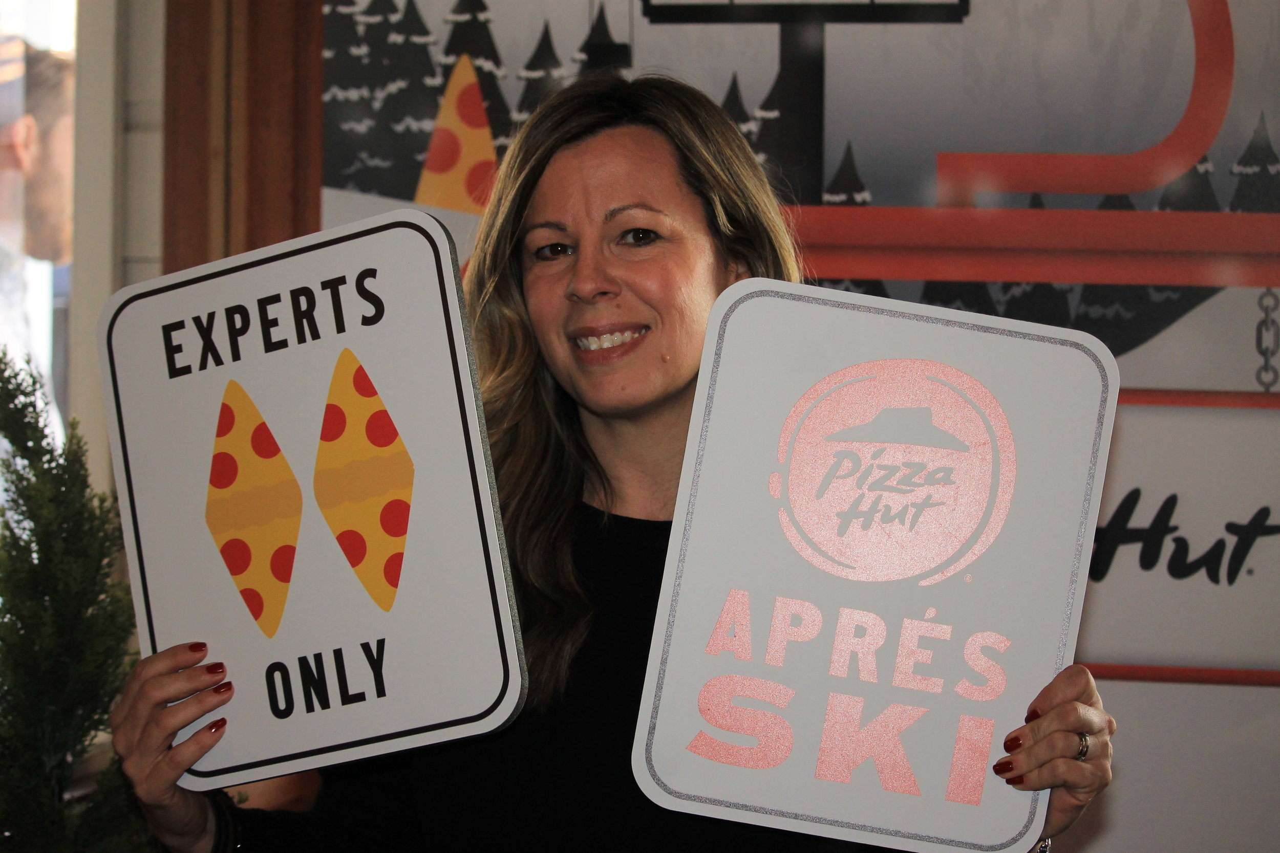 Legion M's Clare Bateman-King with the Pizza Hut photo opp signage.