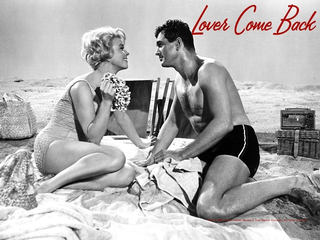 "Doris Day and Rock Hudson look lovingly into each other's eye on the beach from the movie ""Lover Come Back"""