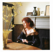 The author in her living room, dressed in a dark green gown, probably a costume from an opera.