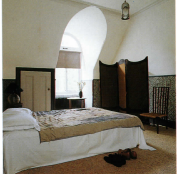 A guest bedroom under the eaves, with a curvaceous Aesthetic Movement screen stretched with roughly hand-woven silk.
