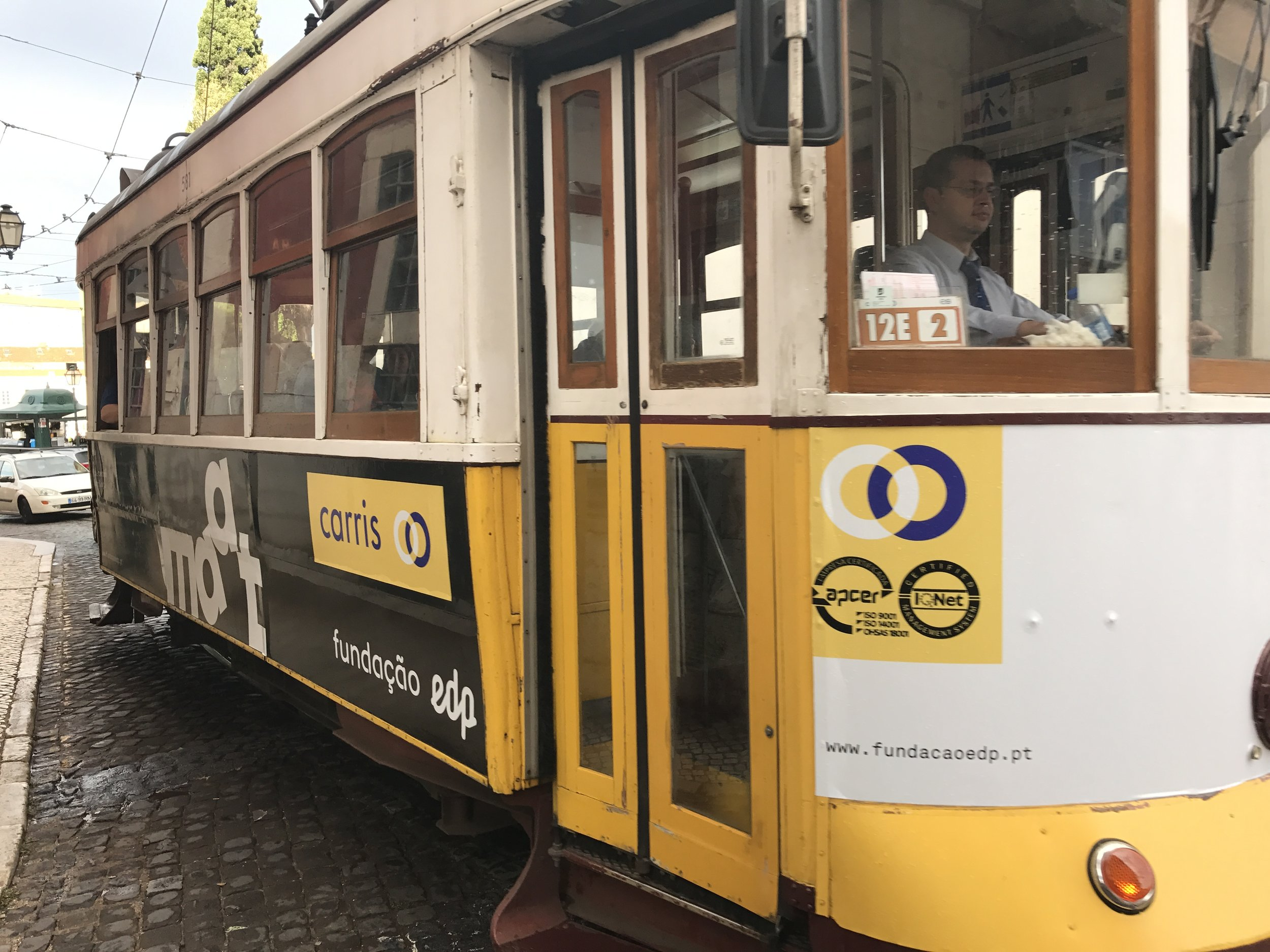 A yellow tram in Alfama District, a key part of the Lisbon culture.