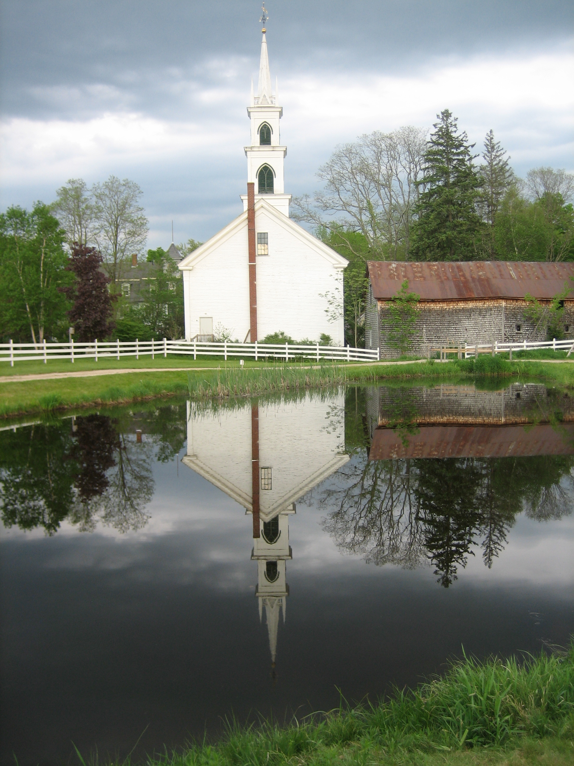 George Blanchette; The Congregational Church reflected in the Remick Museum fish pond.