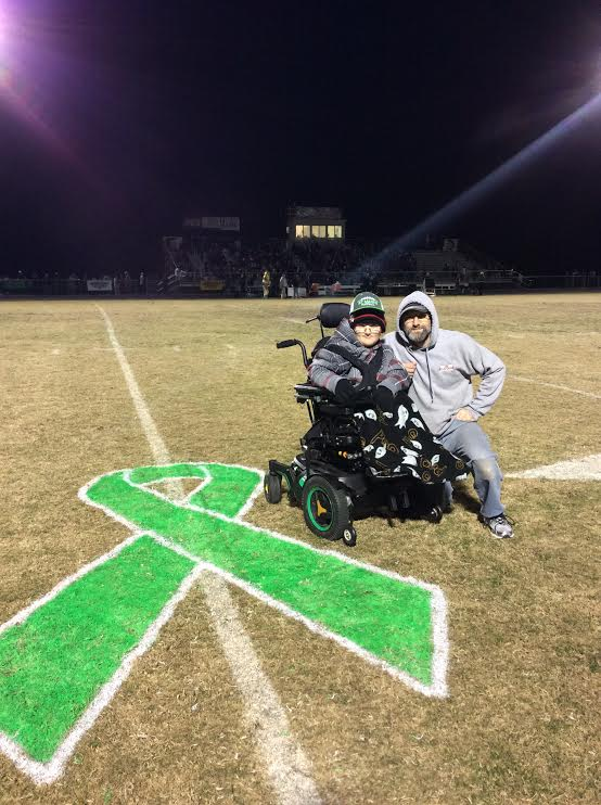 "Saint Mark's High School's Muscle Champion, Mason Nellius, and father, Rich, during halftime at the 2016 Delaware ""Sack Muscle Disease"" Game"