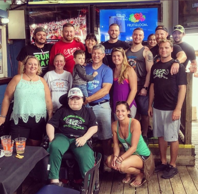 Muscle Movement Fdn. 2018 Delaware Crush Course Committee Members and volunteers take a picture with MMF Muscle Champions, Josh Wallace (front left), and Colty Wallace (held in the arms of grandfather Kenneth Wallace) at the MMF Crush Course after party at The Starboard!