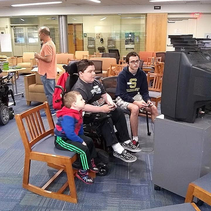 MMF Muscle Champions, Josh and Colty Wallace, enjoy a video game with a student from Salesianum School