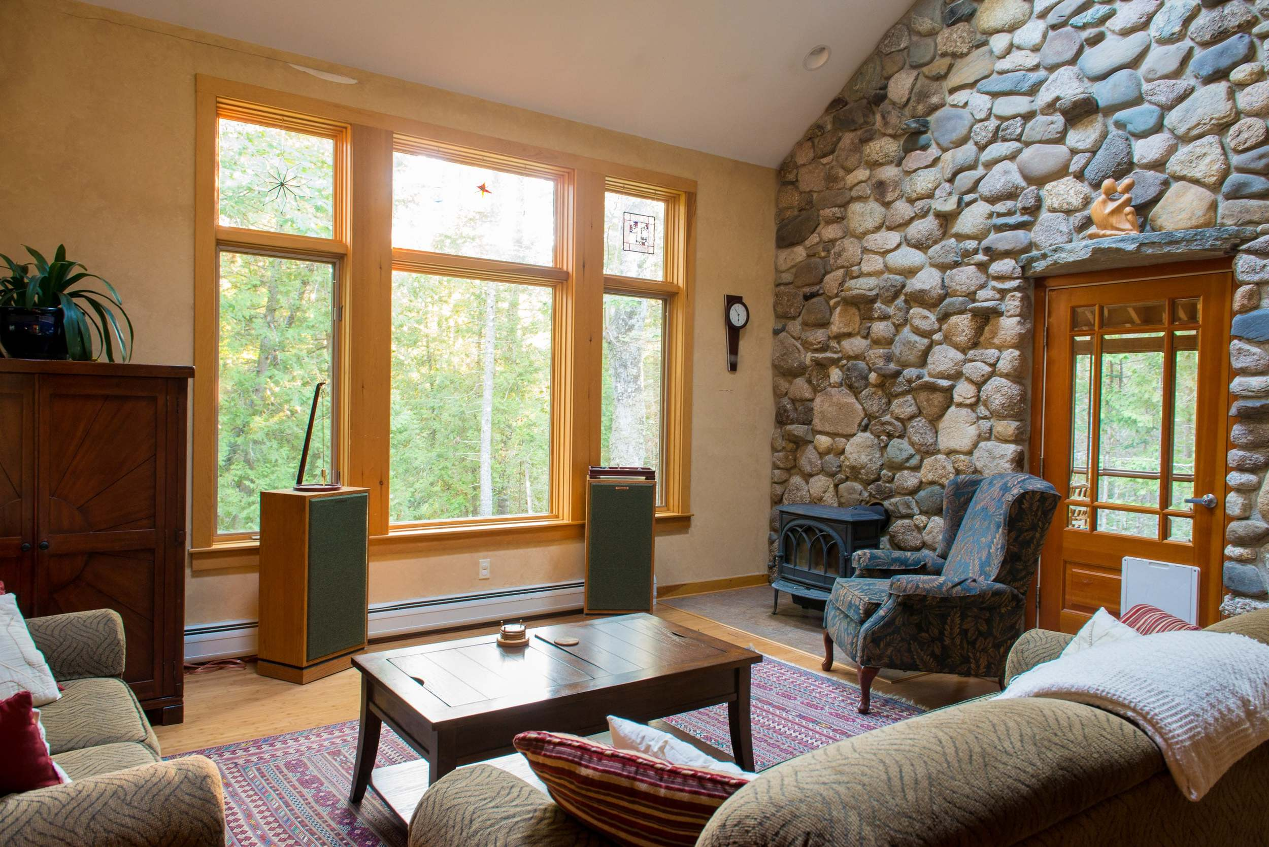 Living room with ample seating, two story native stone wall and porch door.