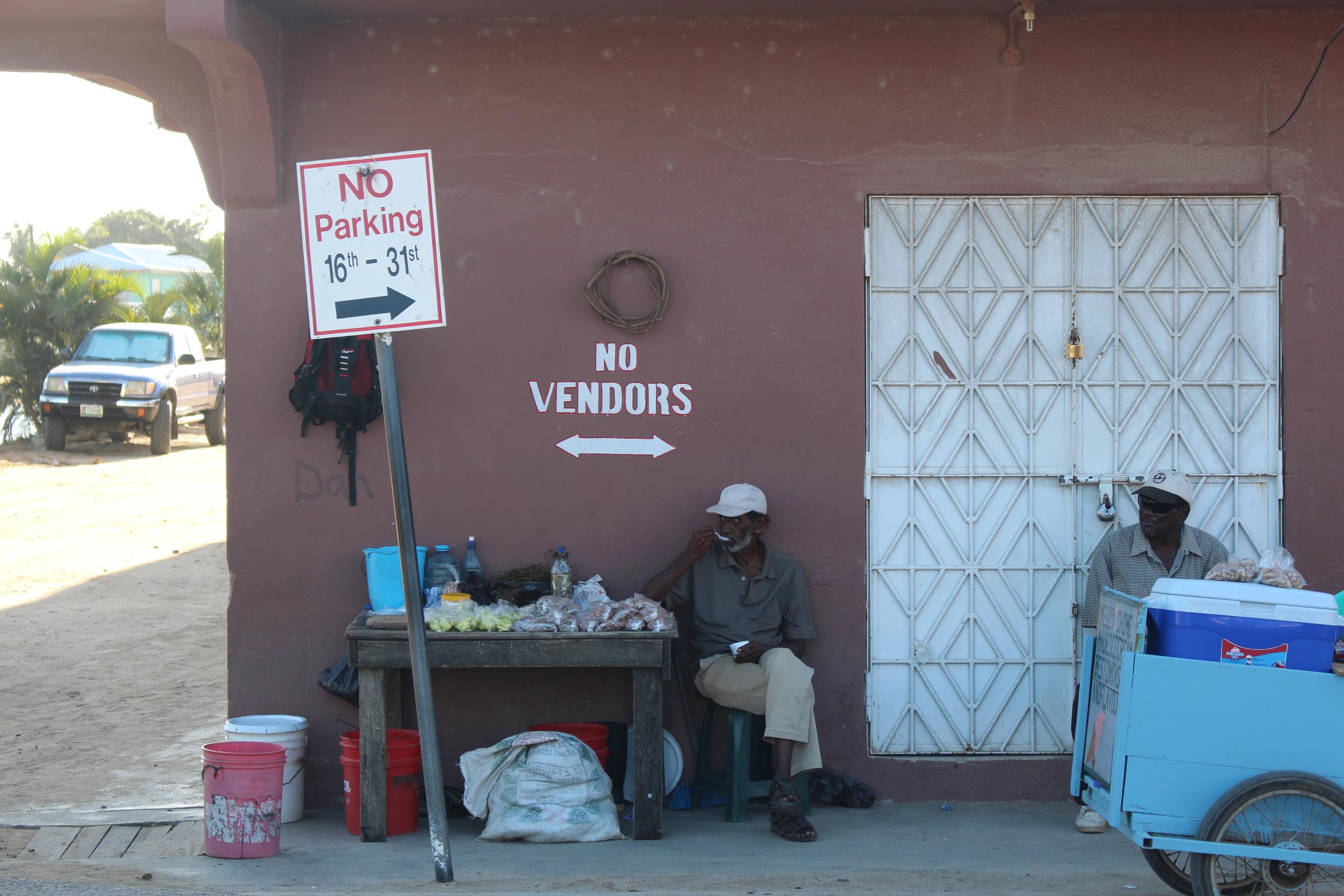 A Belizean vendor delightfully ignores the sign