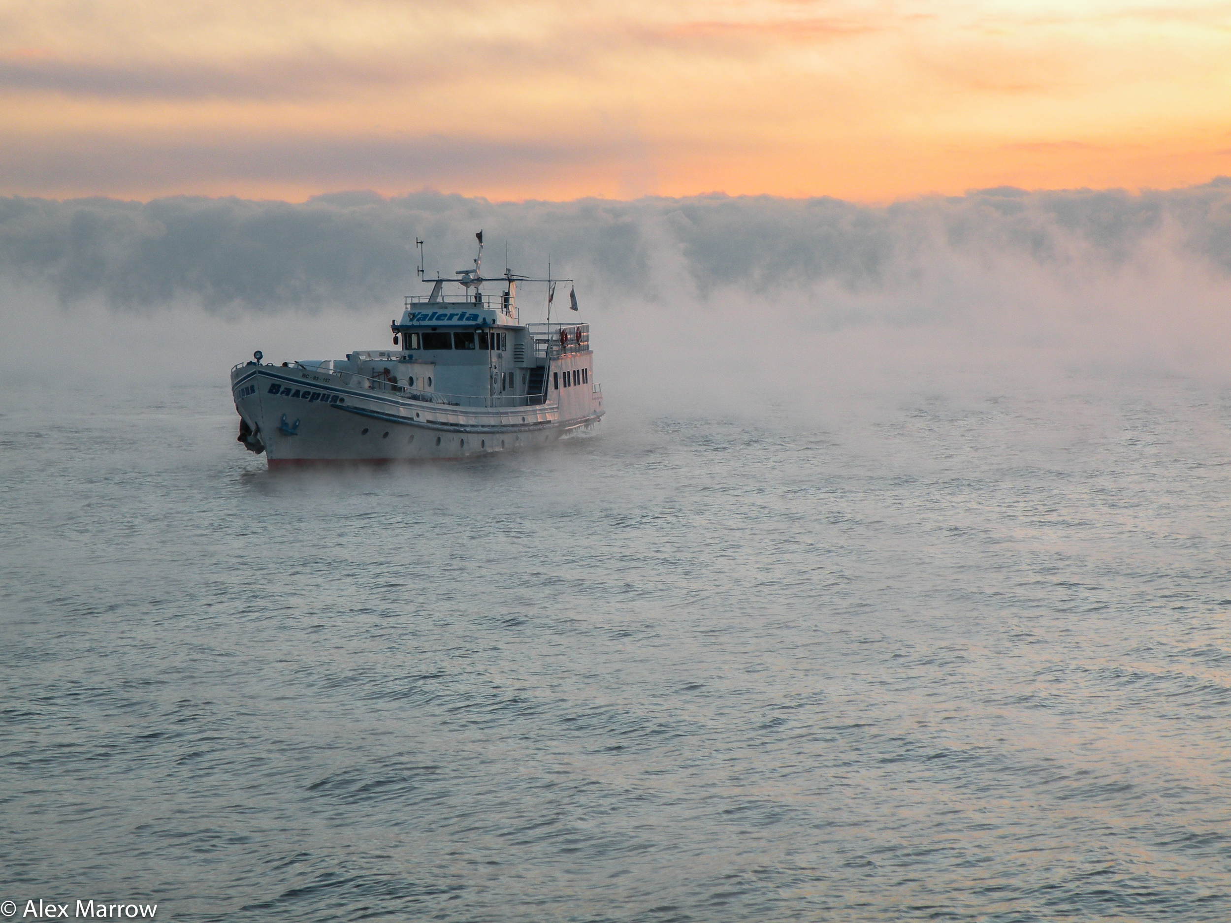 A Boat Cuts Through the Clouds on Lake Baikal