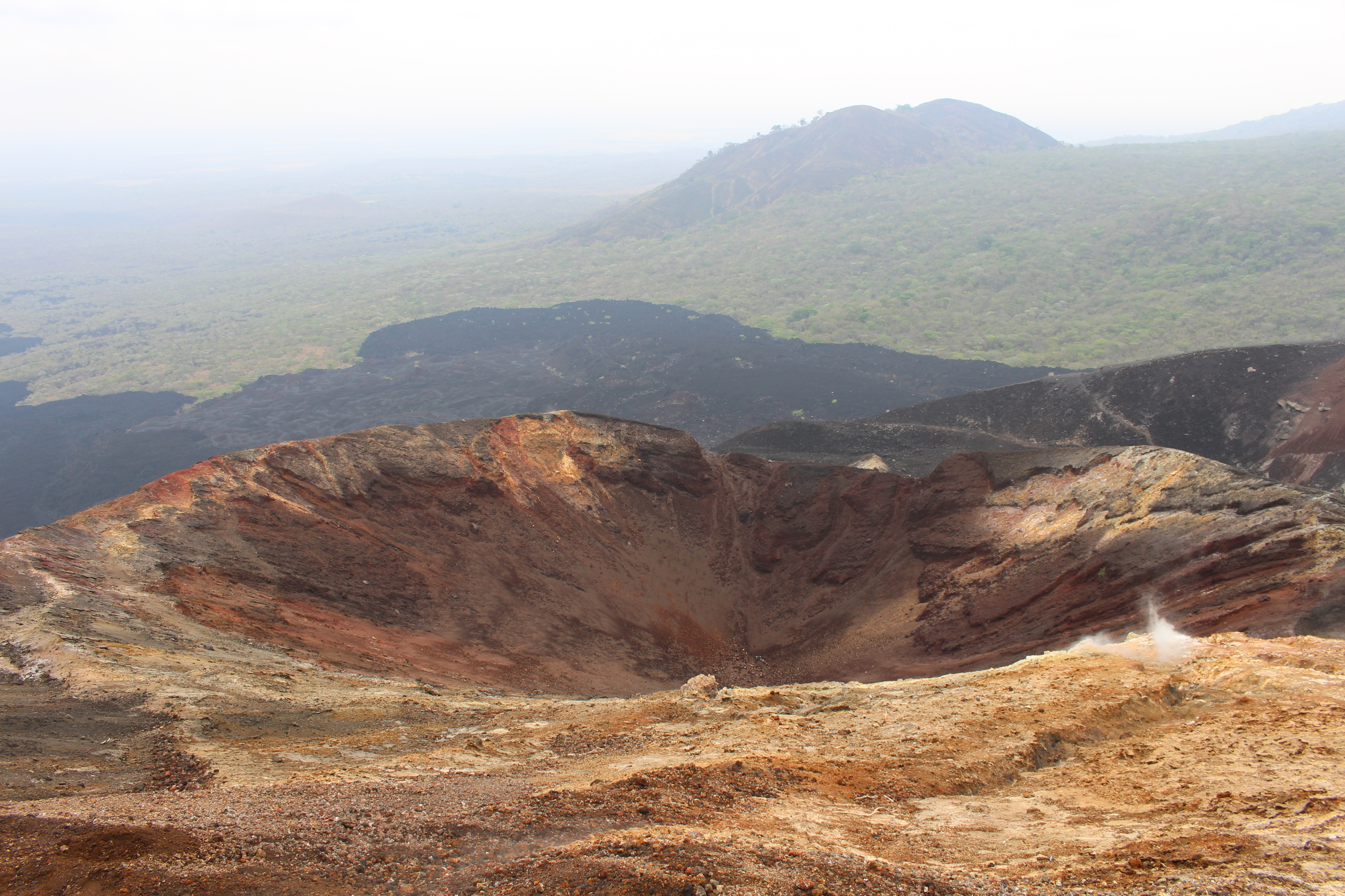 One of Cerro Negro's five craters and the hazy view beyond