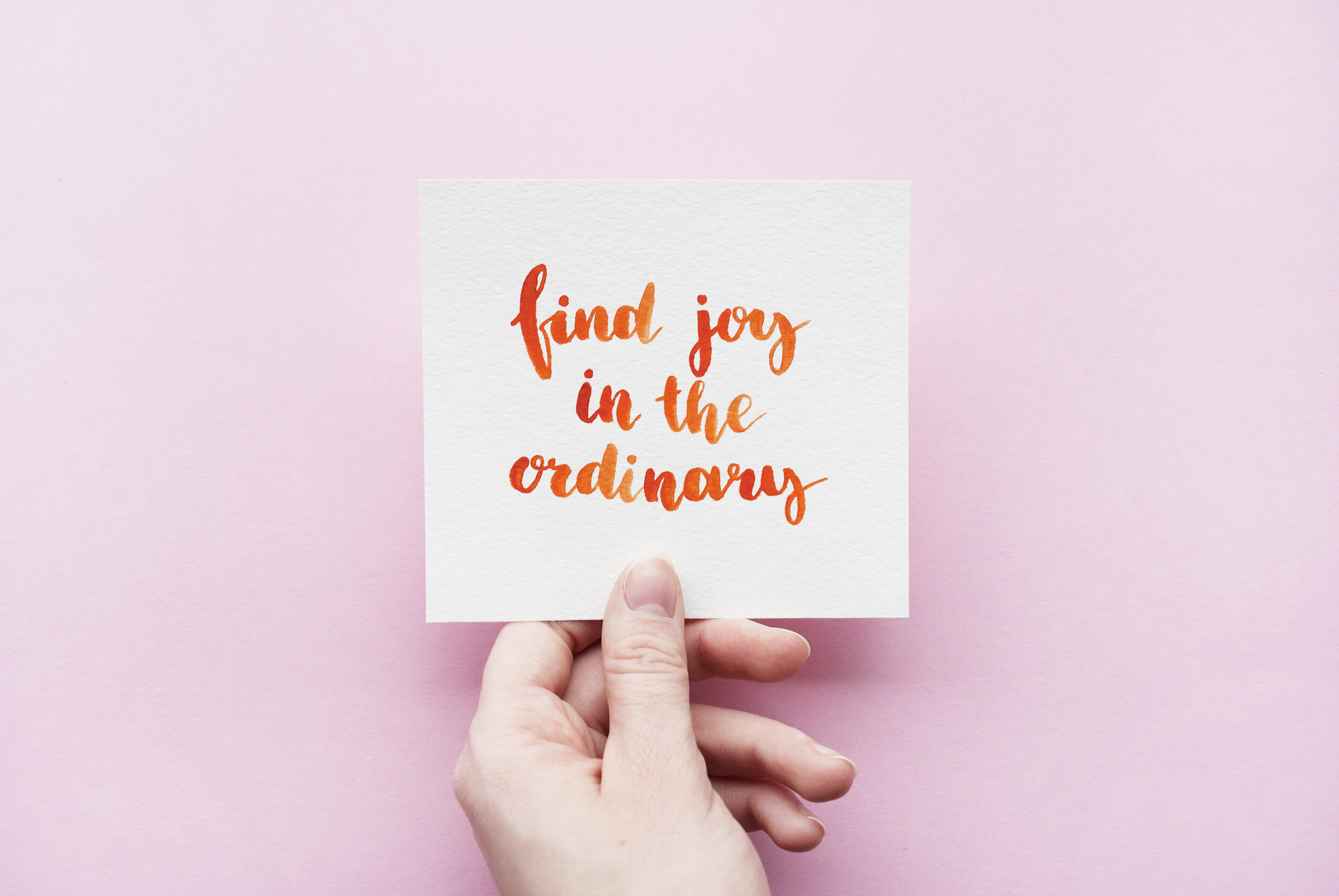 """Minimal composition with girl's hand holding card with inspirational quote """"Find joy in the ordinary"""" written in calligraphy style on paper on a pink background. Flat lay"""