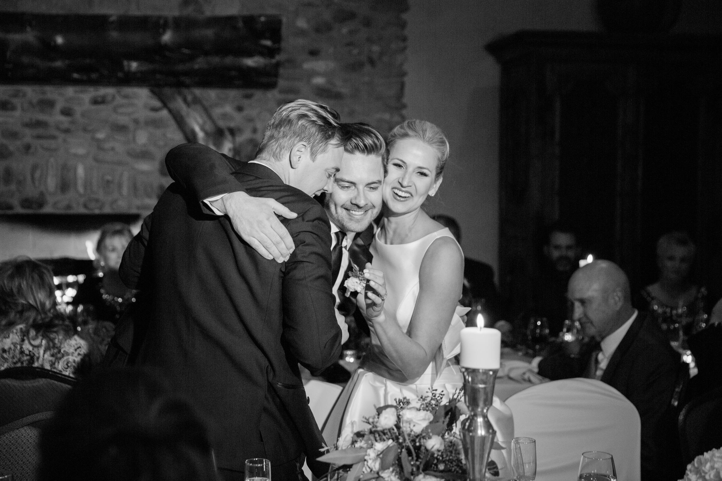 Best man hugging bride and groom