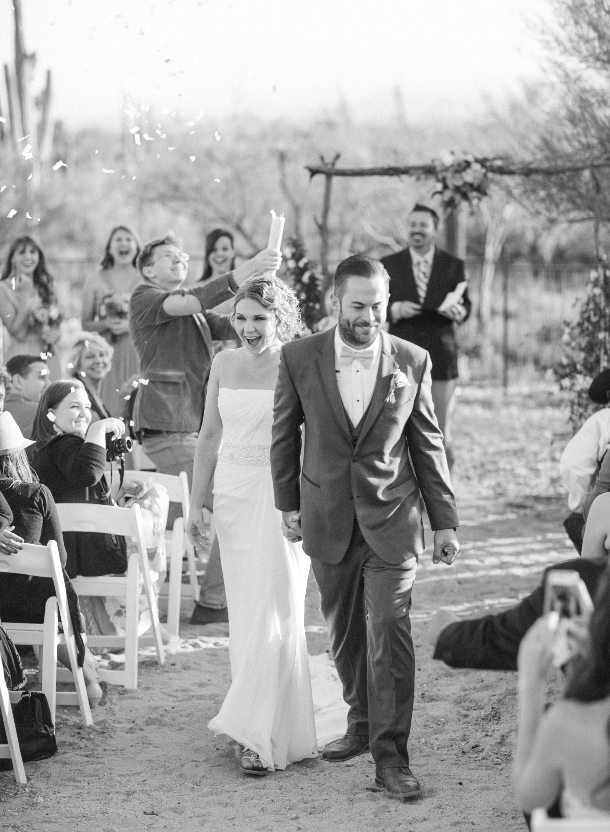 Bride & Groom walking down the aisle with confetti