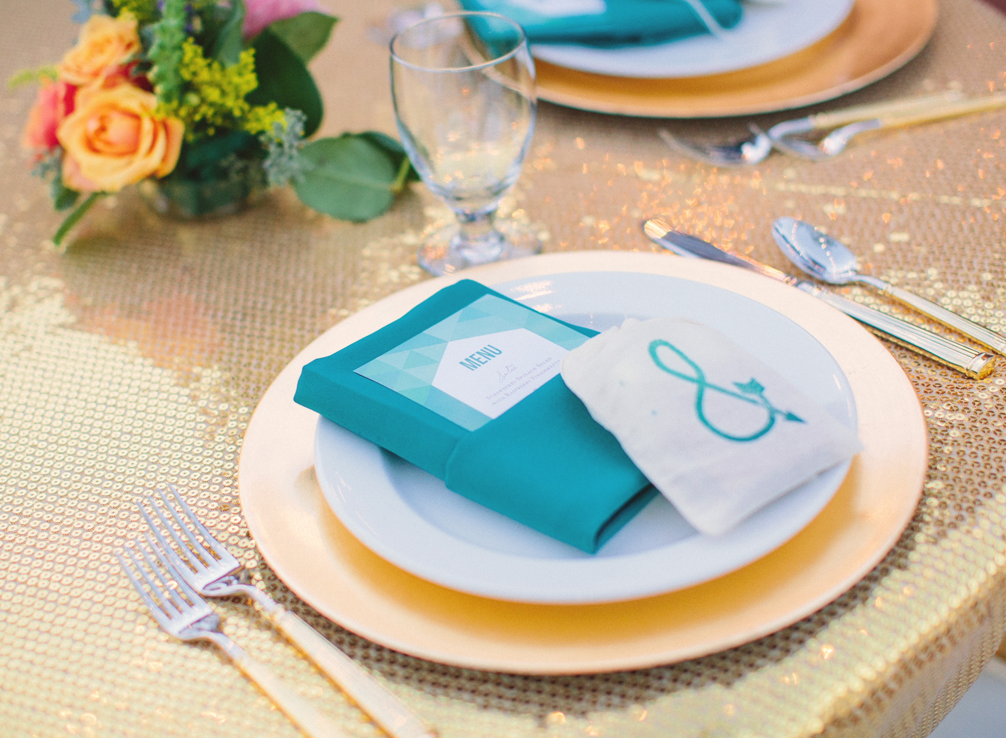 Sweetheart table with gold sequin tablecloth and colorful florals