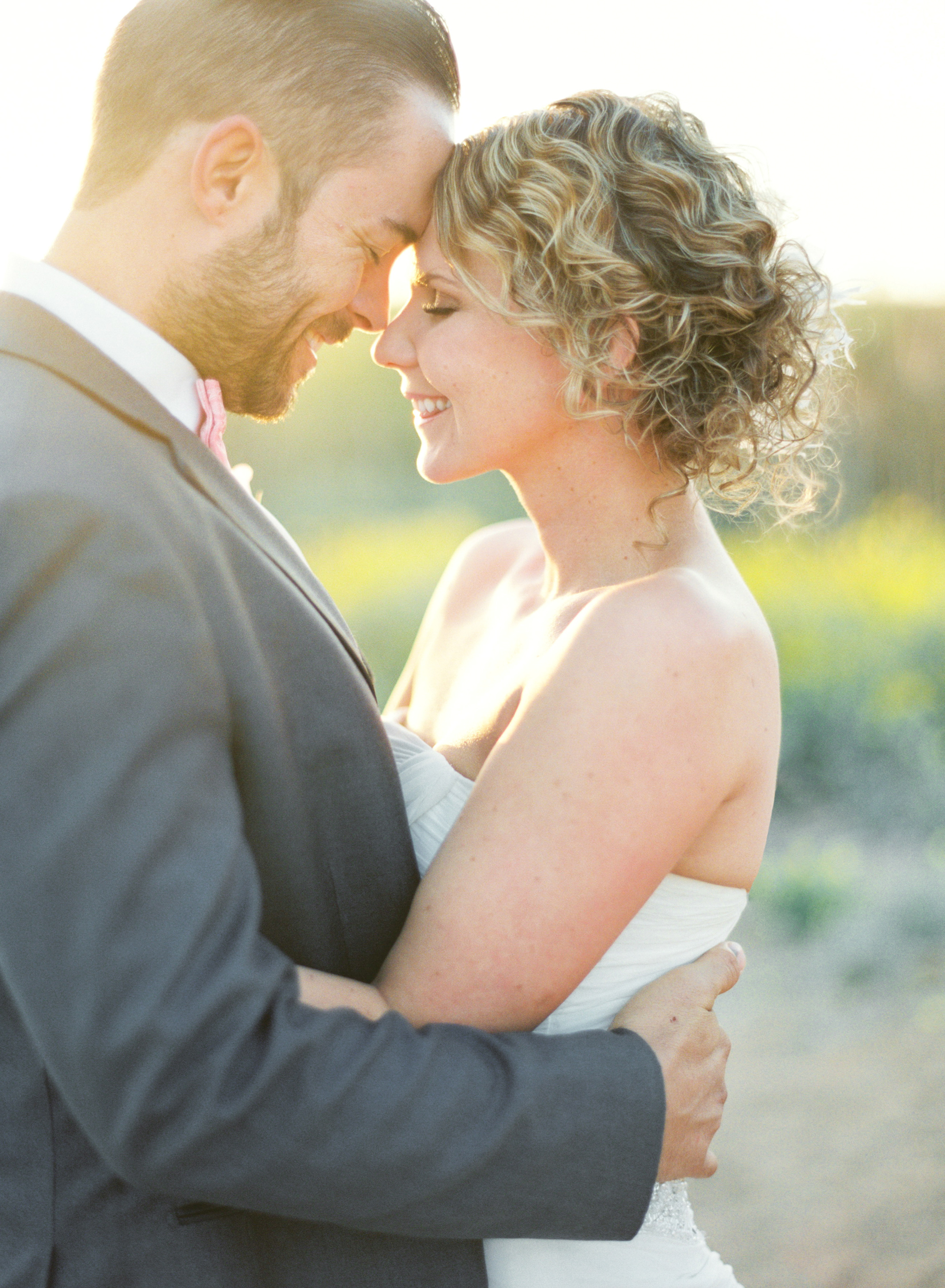 Bride & groom smiling at each other and cuddling