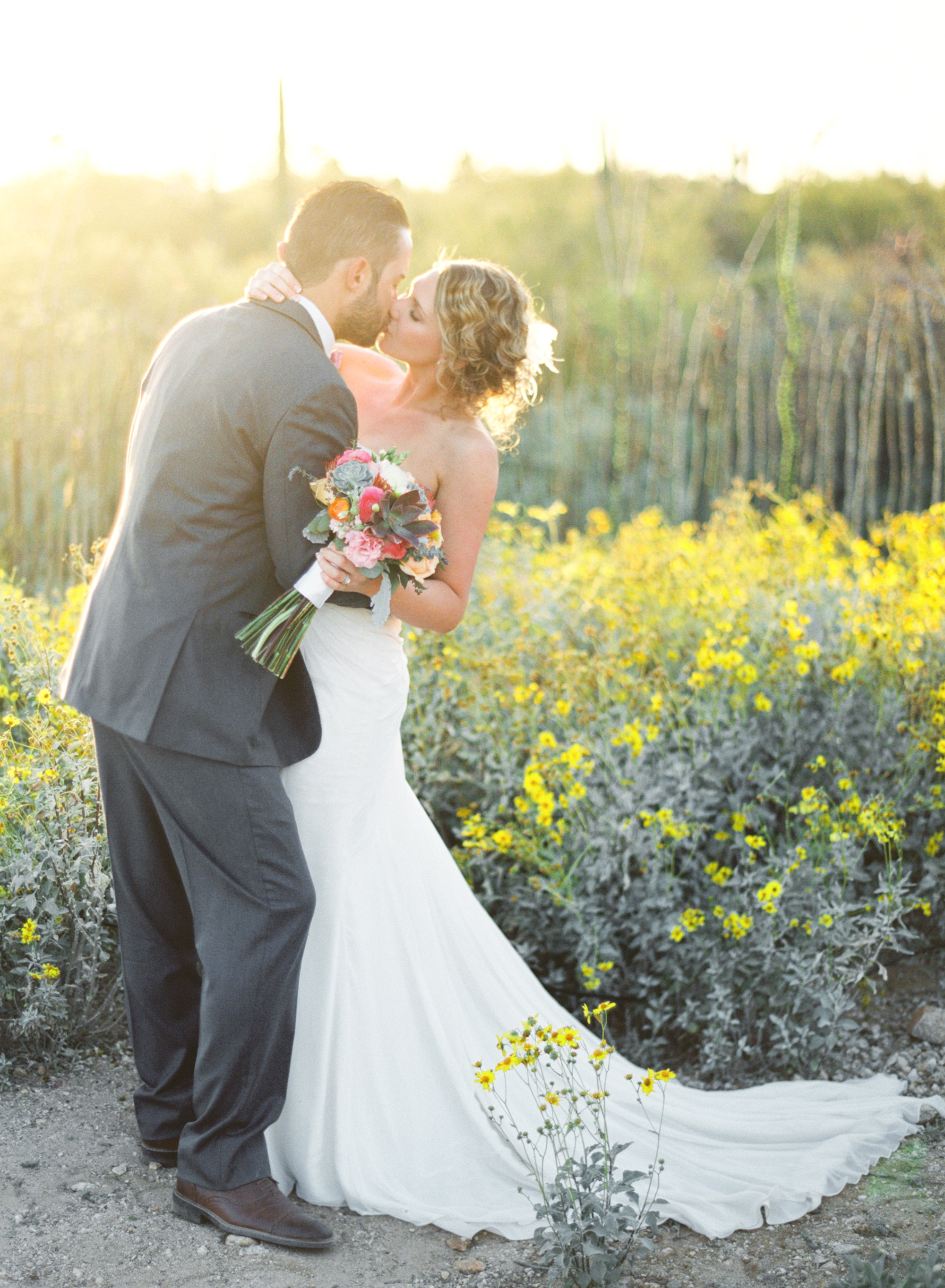 Bride & Groom kissing in wildflowers