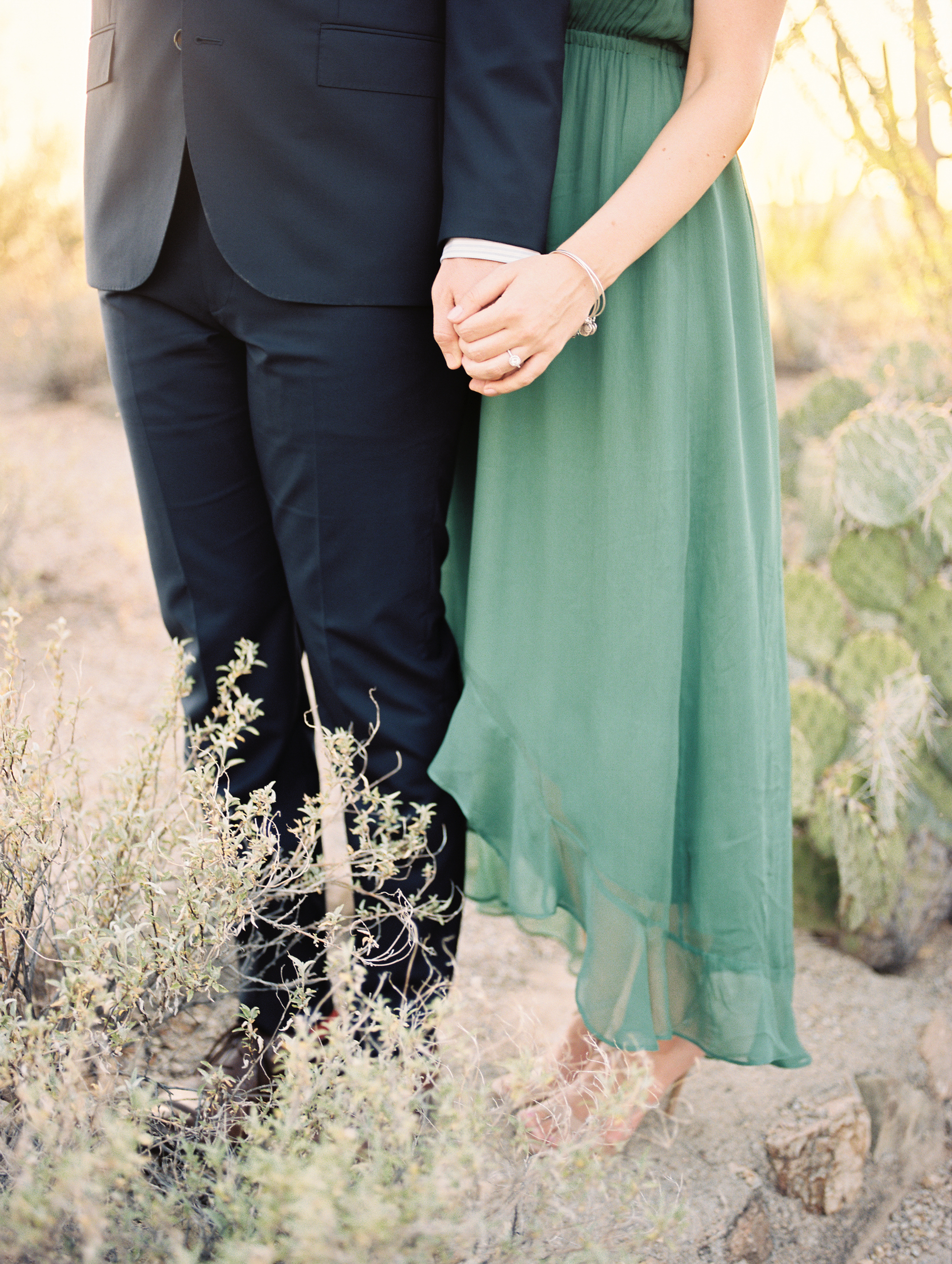 Couple holding hands in the desert at their Tucson engagement session. Gorgeous greens and beautiful engagement ring.
