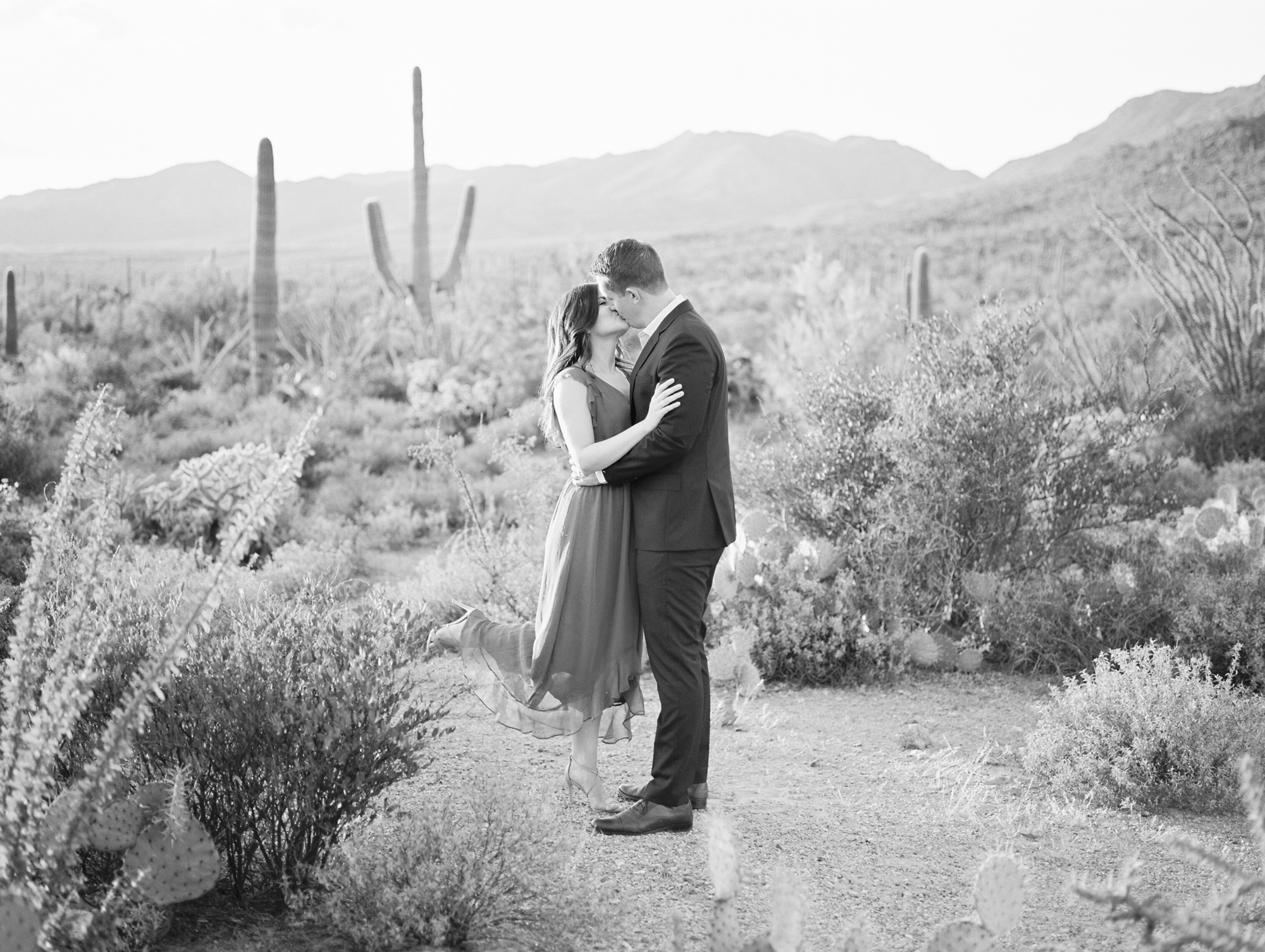 How sweet is this couple kissing in the desert?! This beautiful desert view is to die for and that leg pop is adorable. We love black and white photos, they are so romantic!