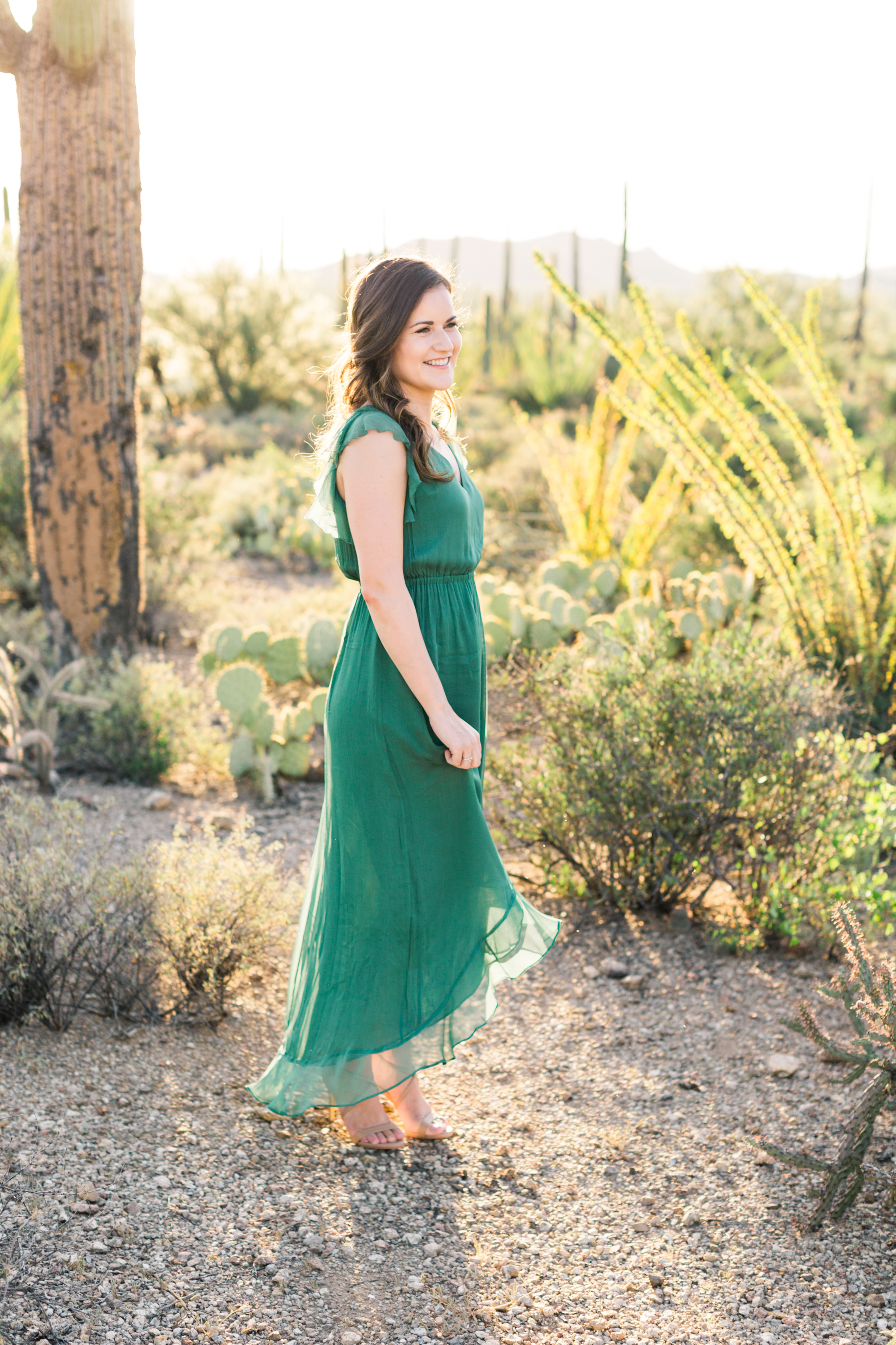 Twirling her beautiful green dress in the desert. Perfect example of what to wear to your engagement session, so elegant.